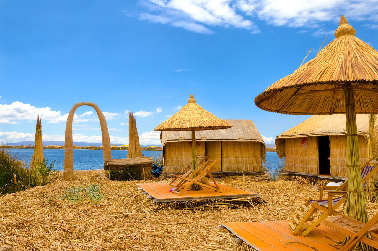 Umbrellas and buildings on one of the Uros Floating Islands on Lake Titicaca in Peru Architecture Beach Colorful Ethnic Floating Houses Inca Isla Island Islands Lake Landscape Manmade Peru Puno Puno, Perú Reed Scene Titicaca Titicaca Lake Totora Tourism Umbrellas Uros Uros Island