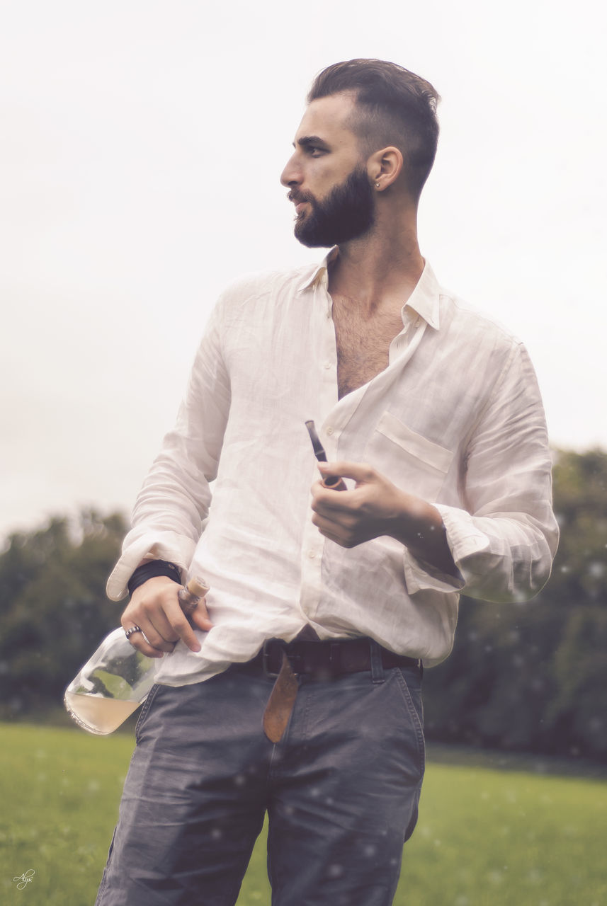 one person, three quarter length, real people, lifestyles, leisure activity, casual clothing, standing, holding, outdoors, young men, young adult, bad habit, day, grass, nature, sky