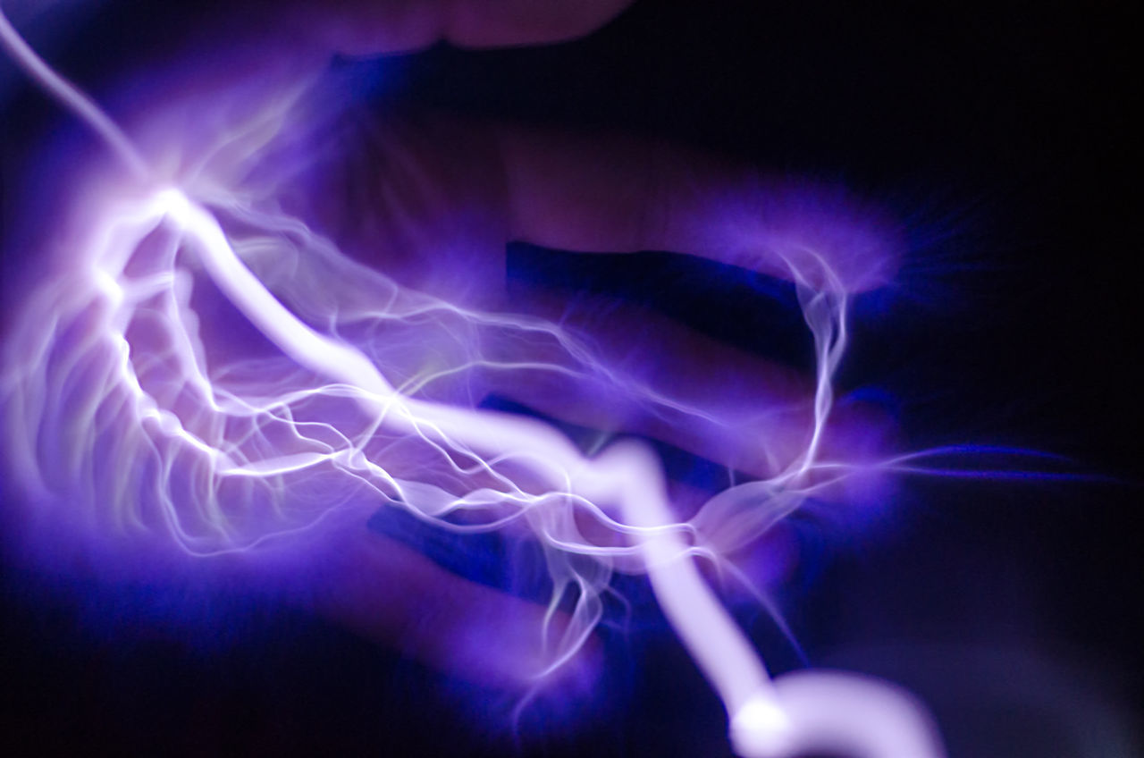 A hand with purple and blue lightning coming out of it Arch Bolt Bright Charge Danger Electric Electricity  Electrocution Energy Finger Fingers Fire Flash Hand Hands Illuminated Light Lightning Power Powerful Shock Spark Sparking  Sparkle Voltage