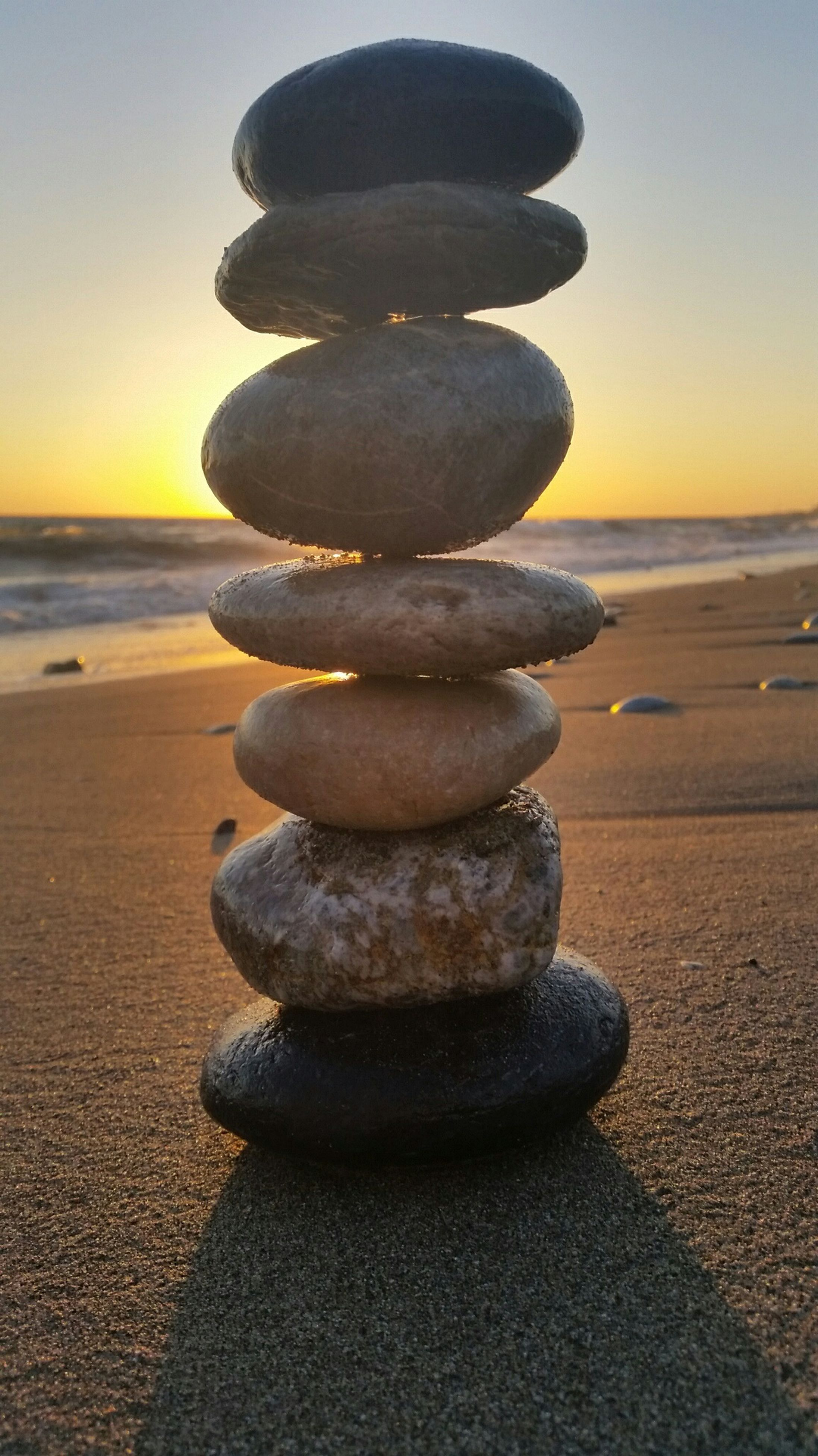 stack, balance, beach, sea, large group of objects, stone - object, pebble, tranquility, shore, horizon over water, sky, in a row, arrangement, focus on foreground, sunlight, sunset, rock - object, sand, clear sky, nature