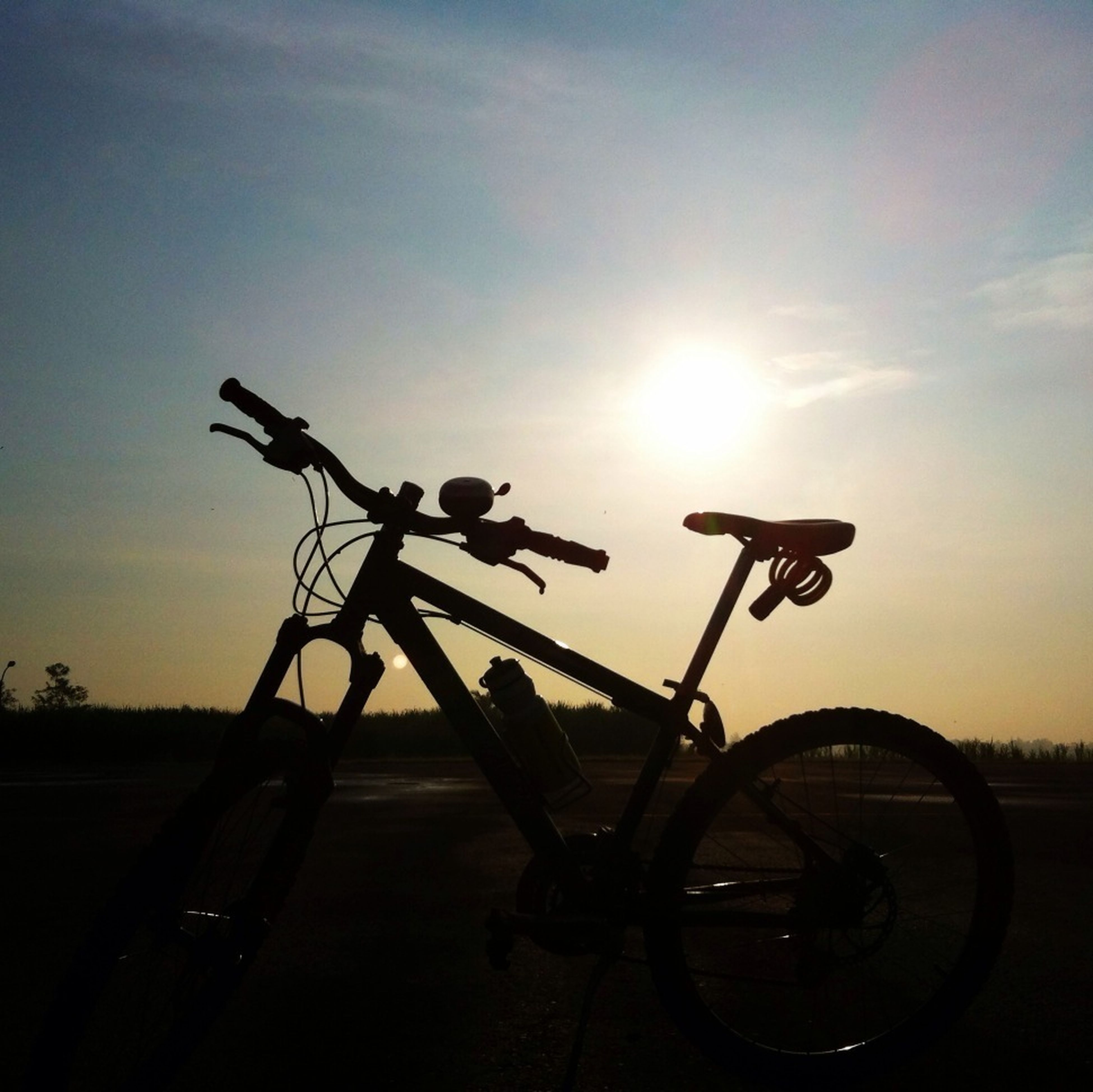 transportation, mode of transport, land vehicle, sunset, sky, bicycle, sun, silhouette, stationary, car, sunlight, cloud - sky, parked, parking, low angle view, sunbeam, road, outdoors, travel, no people