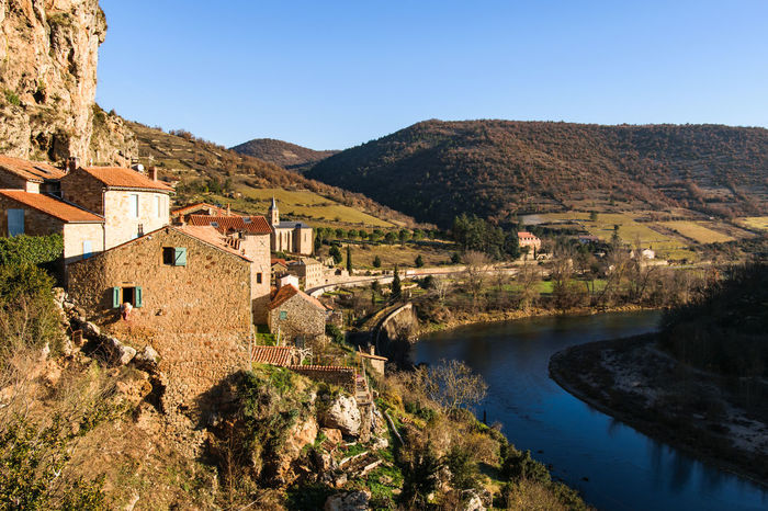 Beautiful view over the village Peyre in France next to the river Tarn at beautiful weather with sunshine and blue sky Archictecture Architecture Aveyron Beauty In Nature Building Built Structure Clear Sky Europe France Historic House Millau Nature No People Peyre Scenics Tarn Water