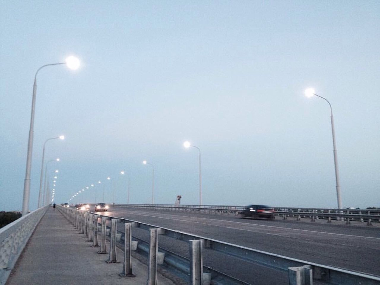 illuminated, street light, lighting equipment, transportation, road, night, railing, the way forward, outdoors, no people, car, built structure, architecture, clear sky, sky, nature, city