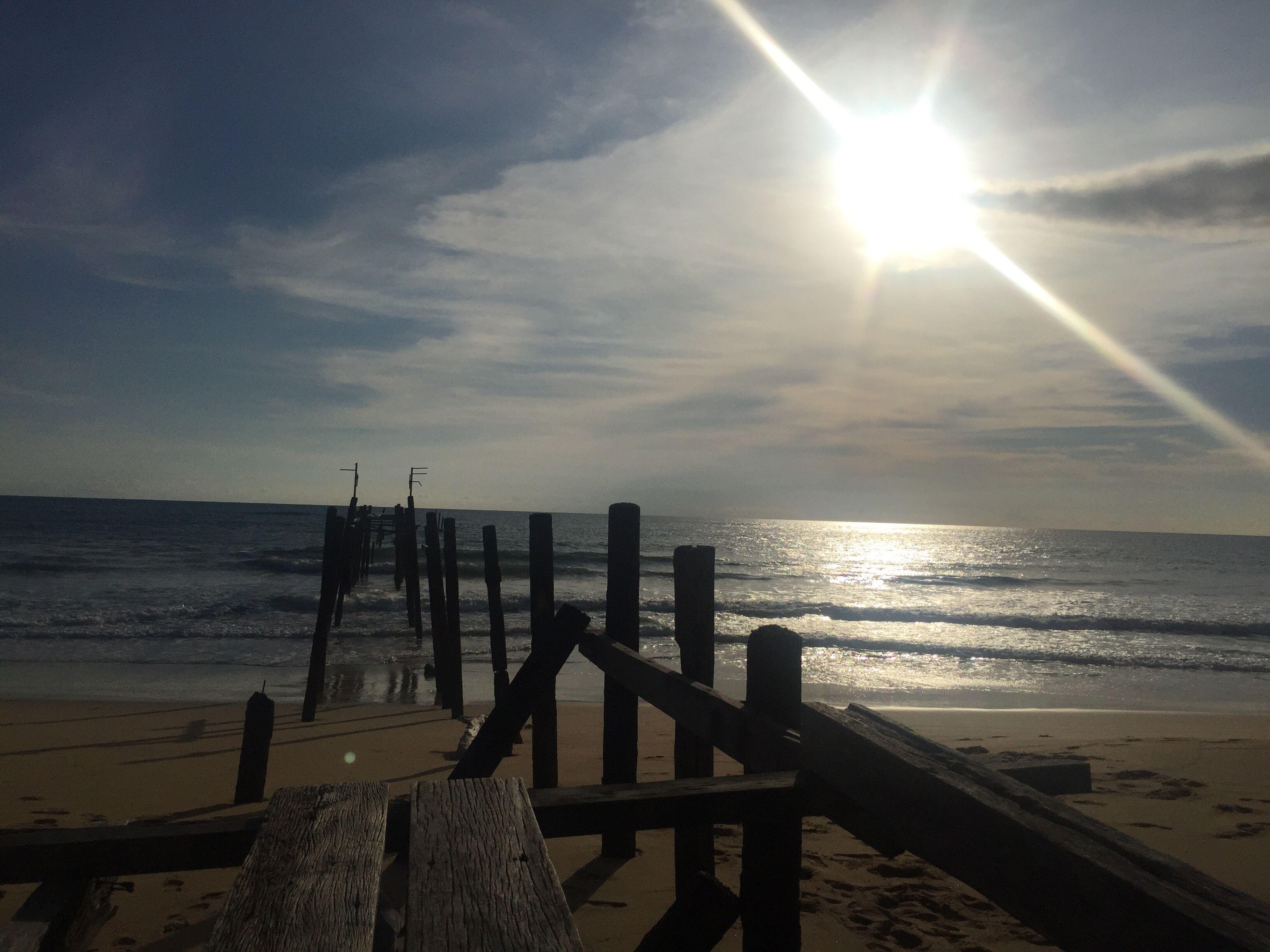 sea, horizon over water, sun, water, tranquil scene, scenics, sky, tranquility, sunlight, sunbeam, beauty in nature, shore, sunset, nature, pier, idyllic, lens flare, outdoors, sunny, remote, cloud - sky, calm, cloud, ocean, non-urban scene, bright, no people, seascape, coastline