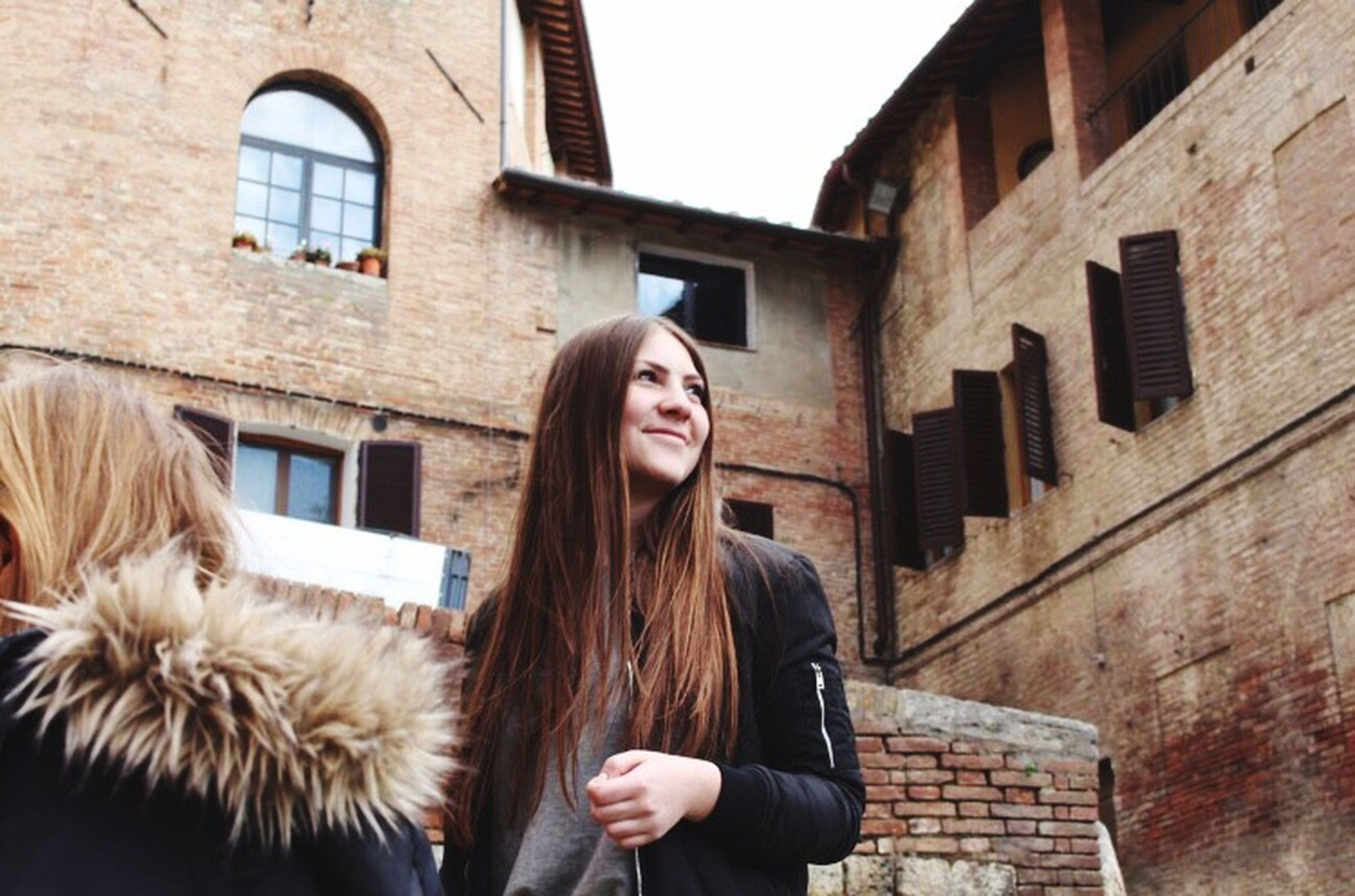 young adult, young women, architecture, built structure, person, long hair, lifestyles, portrait, front view, leisure activity, casual clothing, building, brick wall, day, black hair, outdoors, beauty