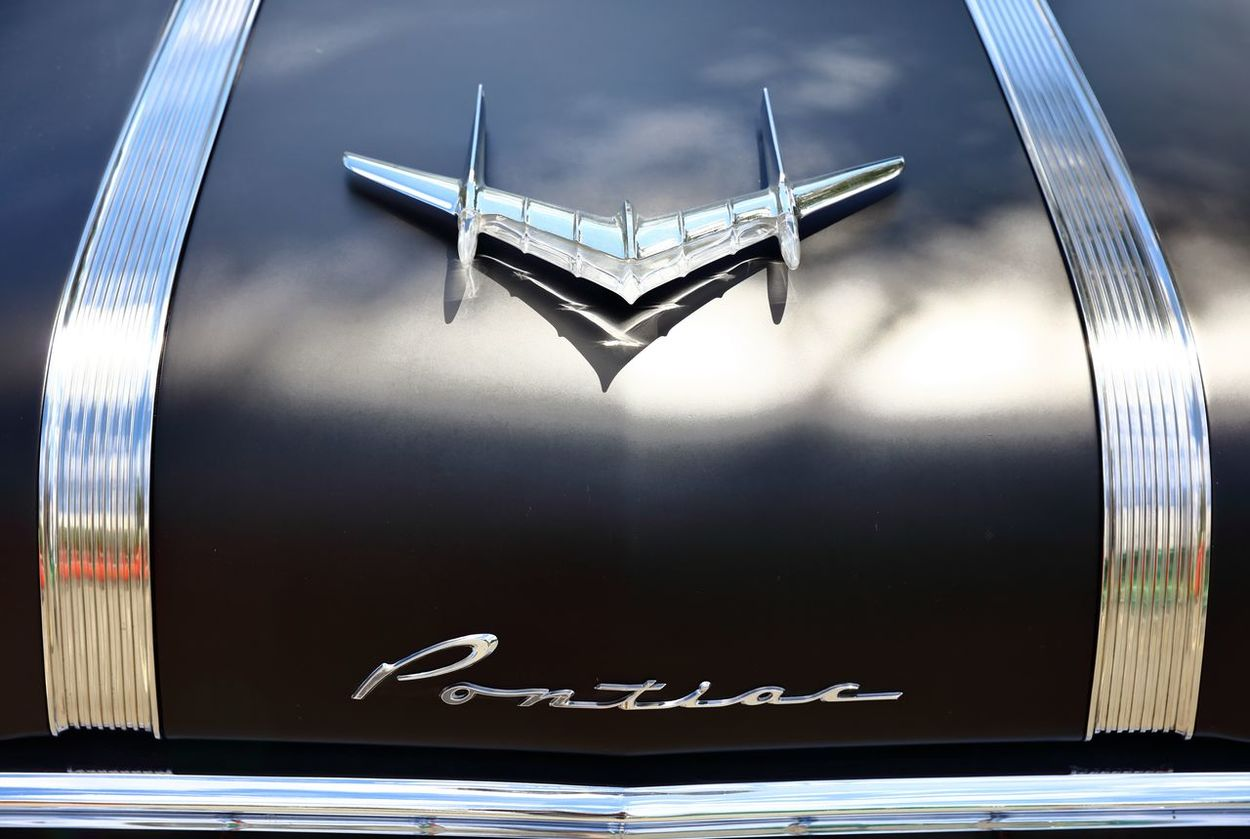 A close up capture of a car bonnet, where the falling midday light created an abstract reflection off of the chrome bonnet emblem, onto the matte black paint. Bonnet Car Car Bonnet Chrome Gleaming Gleaming Light Matte Black Midday Sunlight Pontiac Reflection
