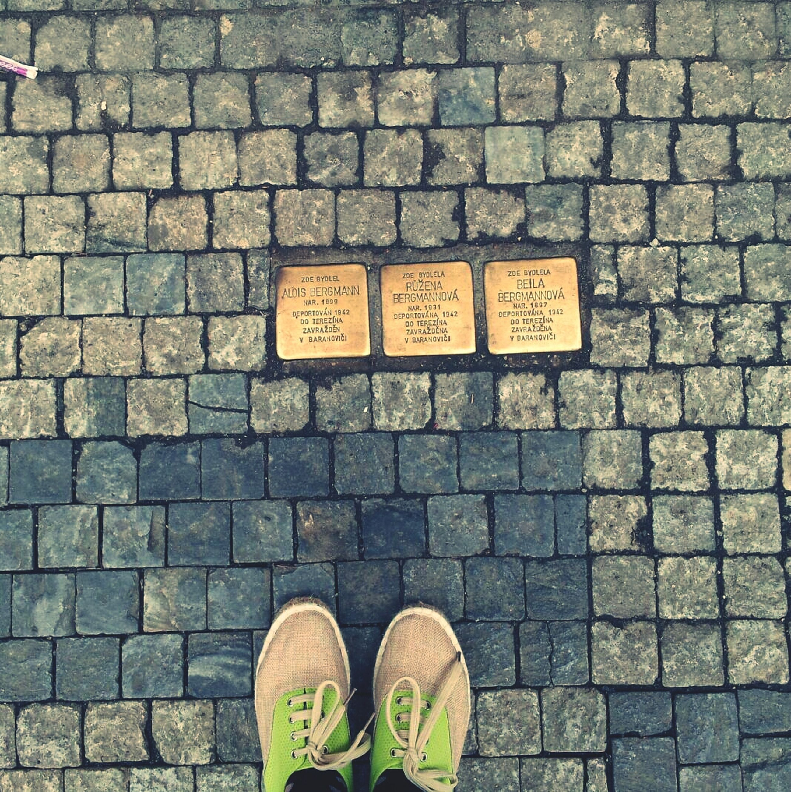 low section, shoe, person, personal perspective, text, standing, communication, western script, footwear, human foot, men, street, lifestyles, cobblestone, non-western script, unrecognizable person, high angle view