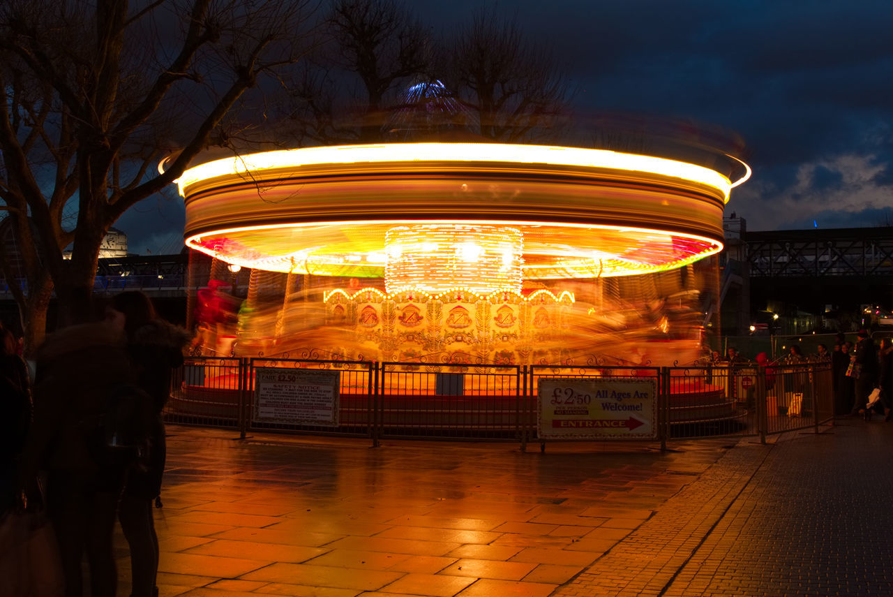Adult Amusement Park Ride Architecture Arts Culture And Entertainment Carousel City Colors Enjoyment Illuminated Leisure Activity Light Light And Shadow Light Effect London Long Exposure Merry-go-round Motion Night Nightlife Outdoors People Rear View Sky