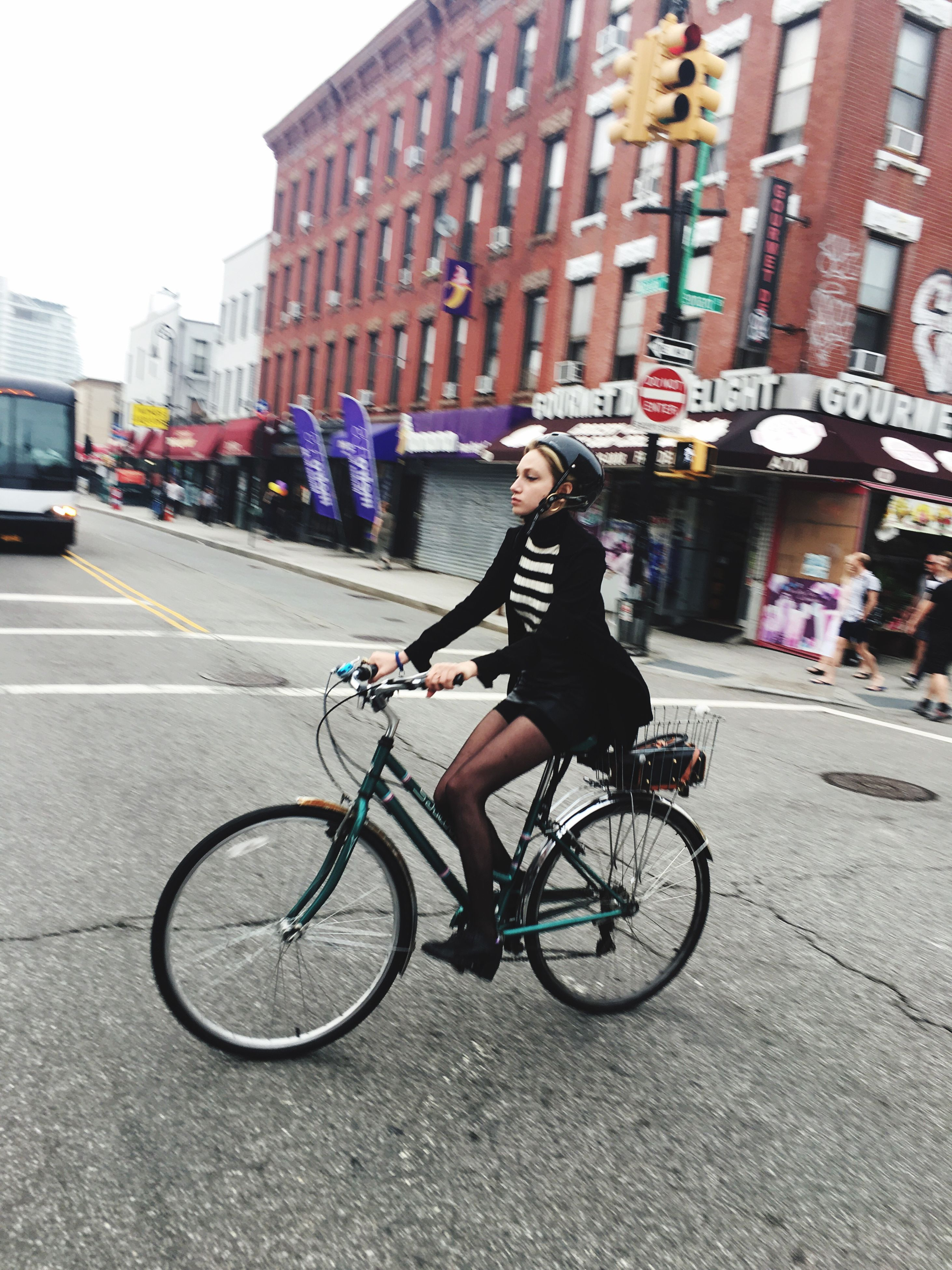 bicycle, transportation, full length, architecture, one person, real people, built structure, building exterior, street, mode of transport, land vehicle, cycling, city, outdoors, lifestyles, riding, casual clothing, city life, day, road, young adult, young women, adult, people
