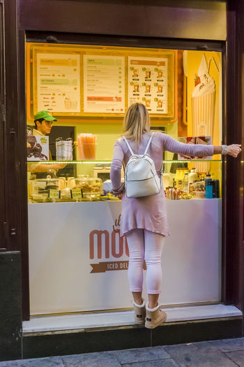 A young woman buying an ice cream in Madrid. City City Life Food And Drink Pink Travel Buying Casual Clothing Customer  Food Full Length Ice Cream Leisure Activity Lifestyles One Person Outdoors People Real People Rear View Retail  Store Take Away Tourism Women Young Adult Young Women