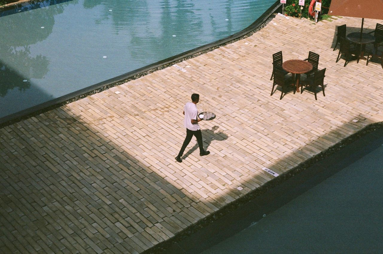 Barman serving drinks between two pool. Bar Barman Day Drinking Film Film Photography Filmcamera Filmisnotdead Hotel Leisure Activity Lifestyles Outdoors Pool Poolside Poolview Serving SriLanka Sunlight Sunny Table Tropical Climate