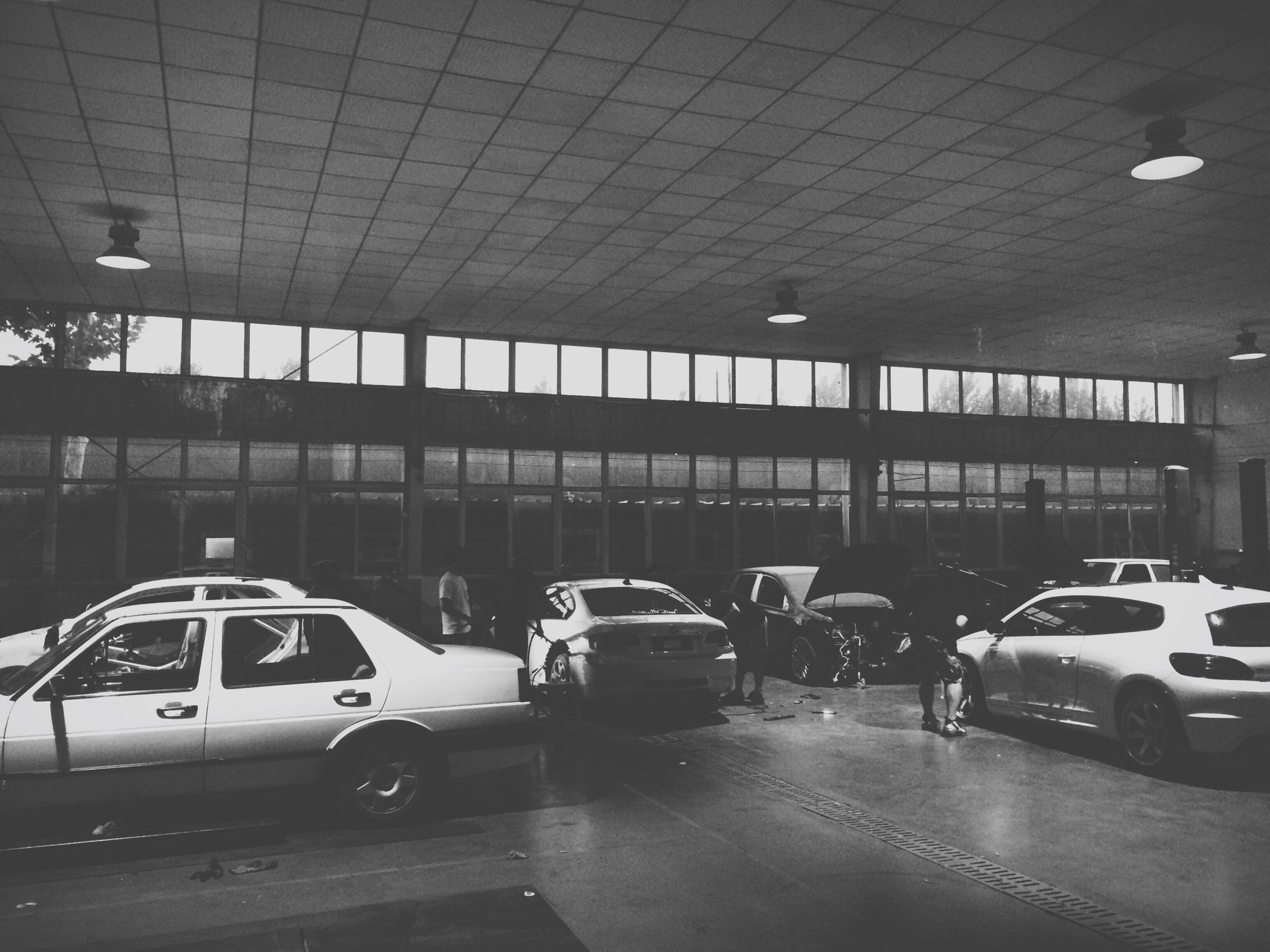 transportation, land vehicle, mode of transport, car, architecture, built structure, road, street, travel, indoors, city, road marking, on the move, parking lot, illuminated, city life, incidental people, stationary, airport, ceiling