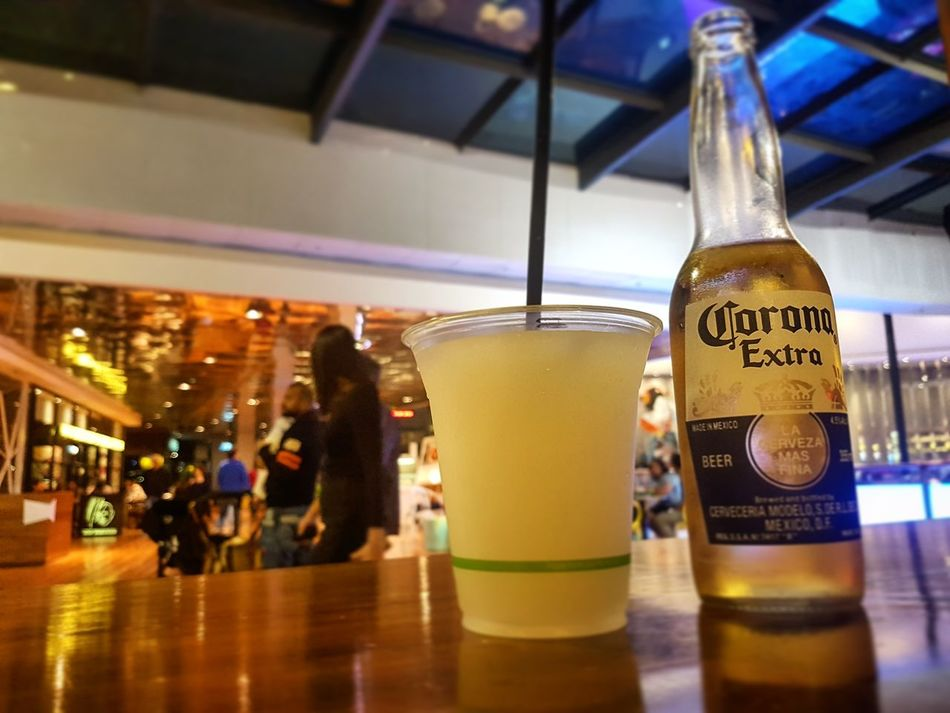 Coronaextra Corona Beer FrozenMargaritas Frozenmargarita Western Script Food And Drink Text Communication Indoors  Glass - Material Close-up Focus On Foreground Person Retail  Freshness Couple Chat Before MOVIE