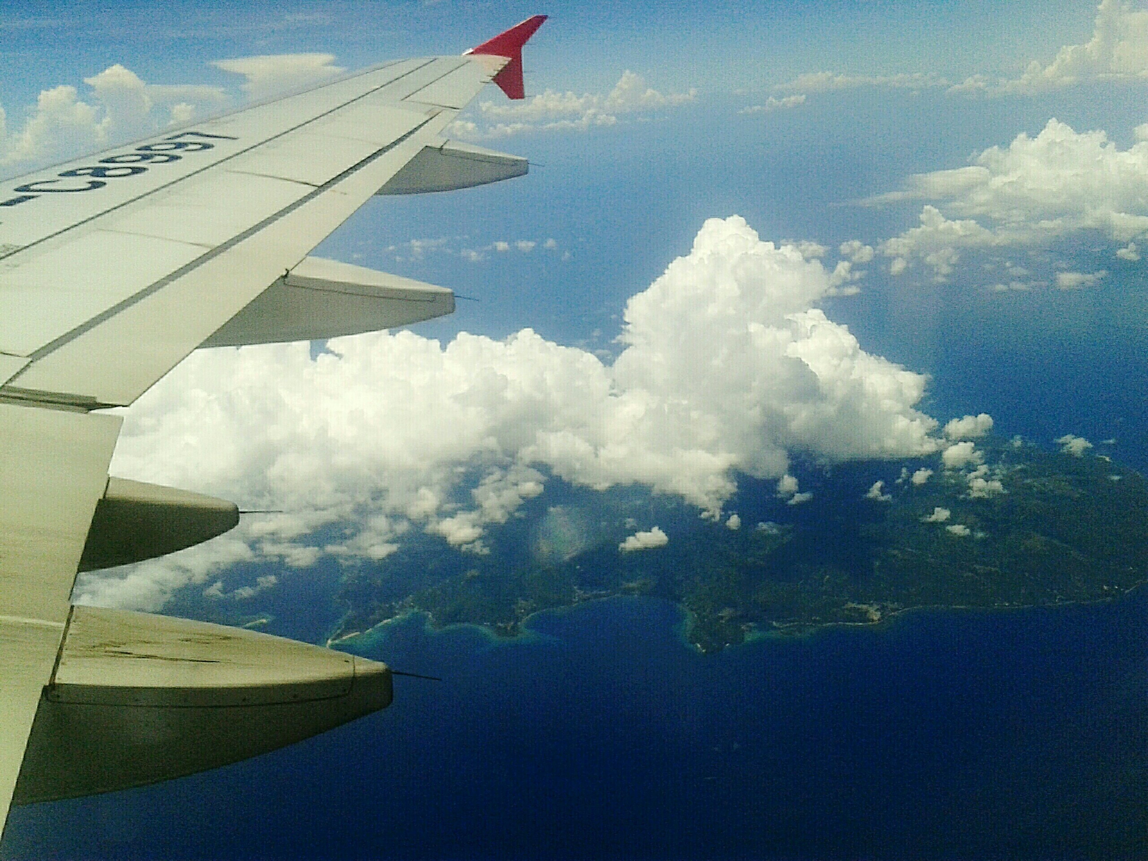 transportation, mode of transport, flying, aircraft wing, airplane, air vehicle, part of, cropped, mid-air, aerial view, travel, nautical vessel, sky, journey, on the move, water, cloud - sky, sea, nature, day