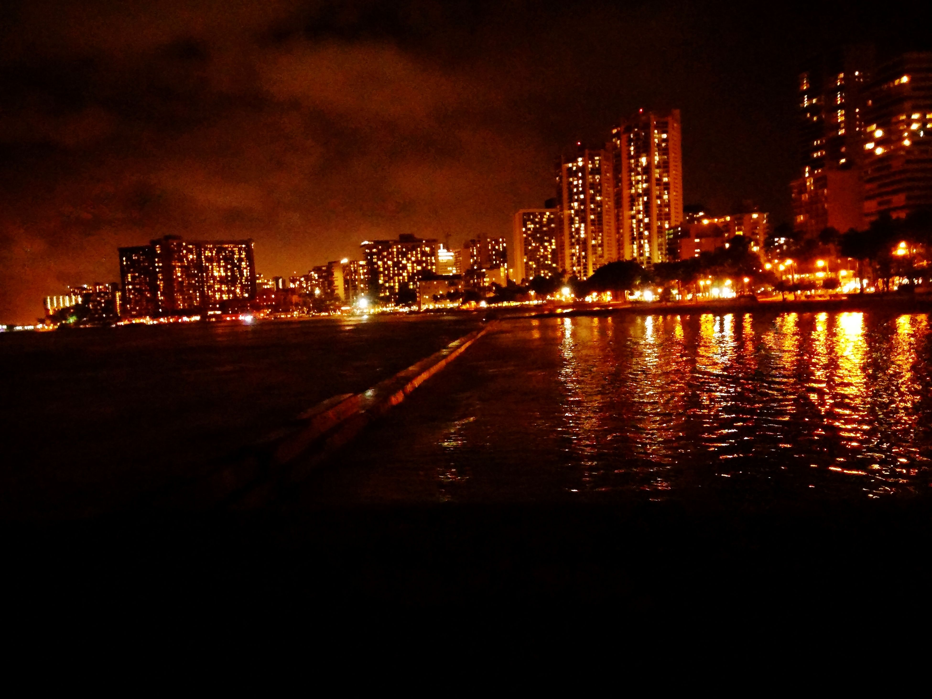 illuminated, night, building exterior, city, architecture, water, built structure, cityscape, sky, river, waterfront, reflection, long exposure, skyscraper, city life, light - natural phenomenon, urban skyline, sea, residential building, lighting equipment