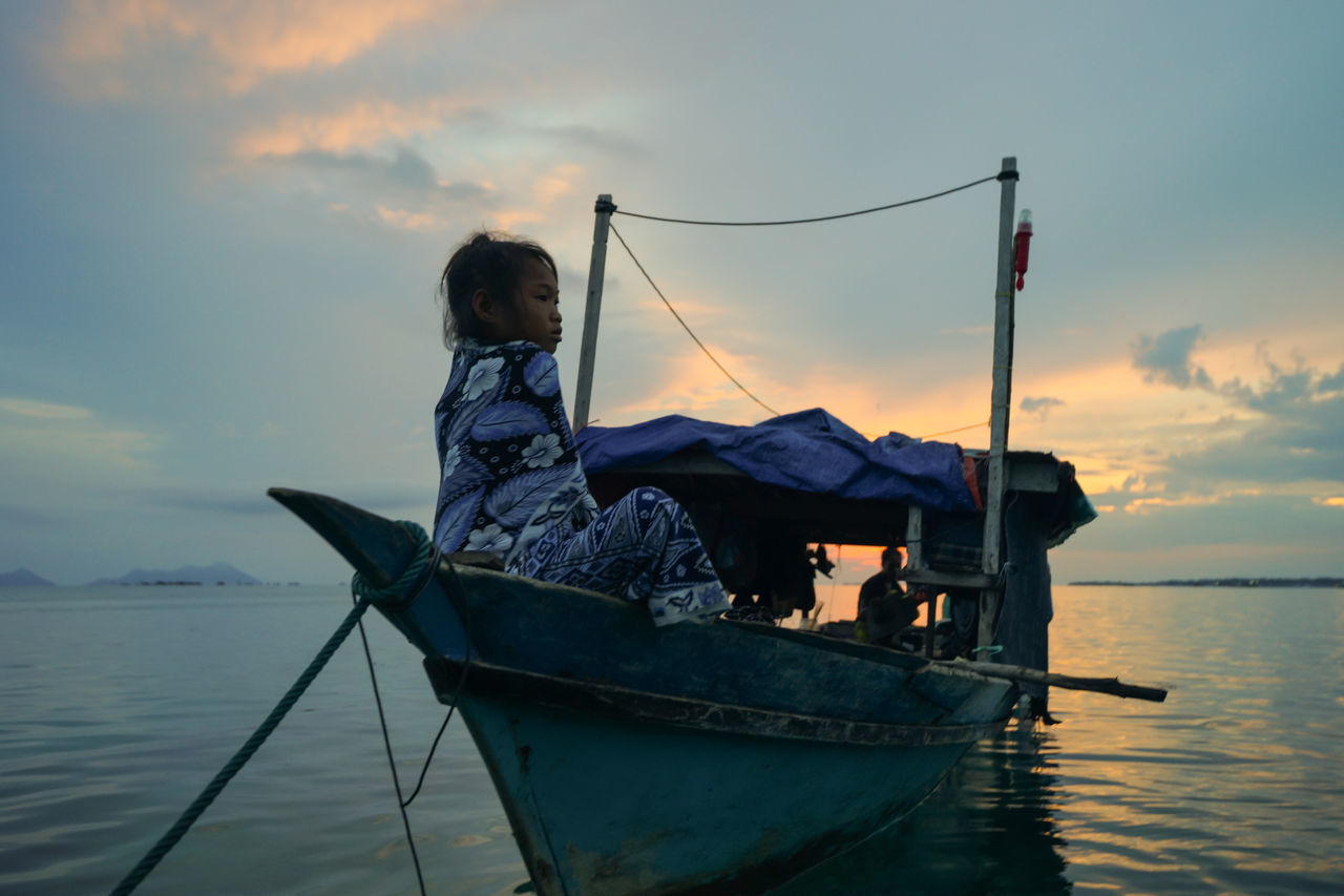 nautical vessel, transportation, water, mode of transport, sky, boat, one person, cloud - sky, sunset, nature, real people, sea, outdoors, standing, childhood, sitting, beauty in nature, day, sailing, full length, oar, people