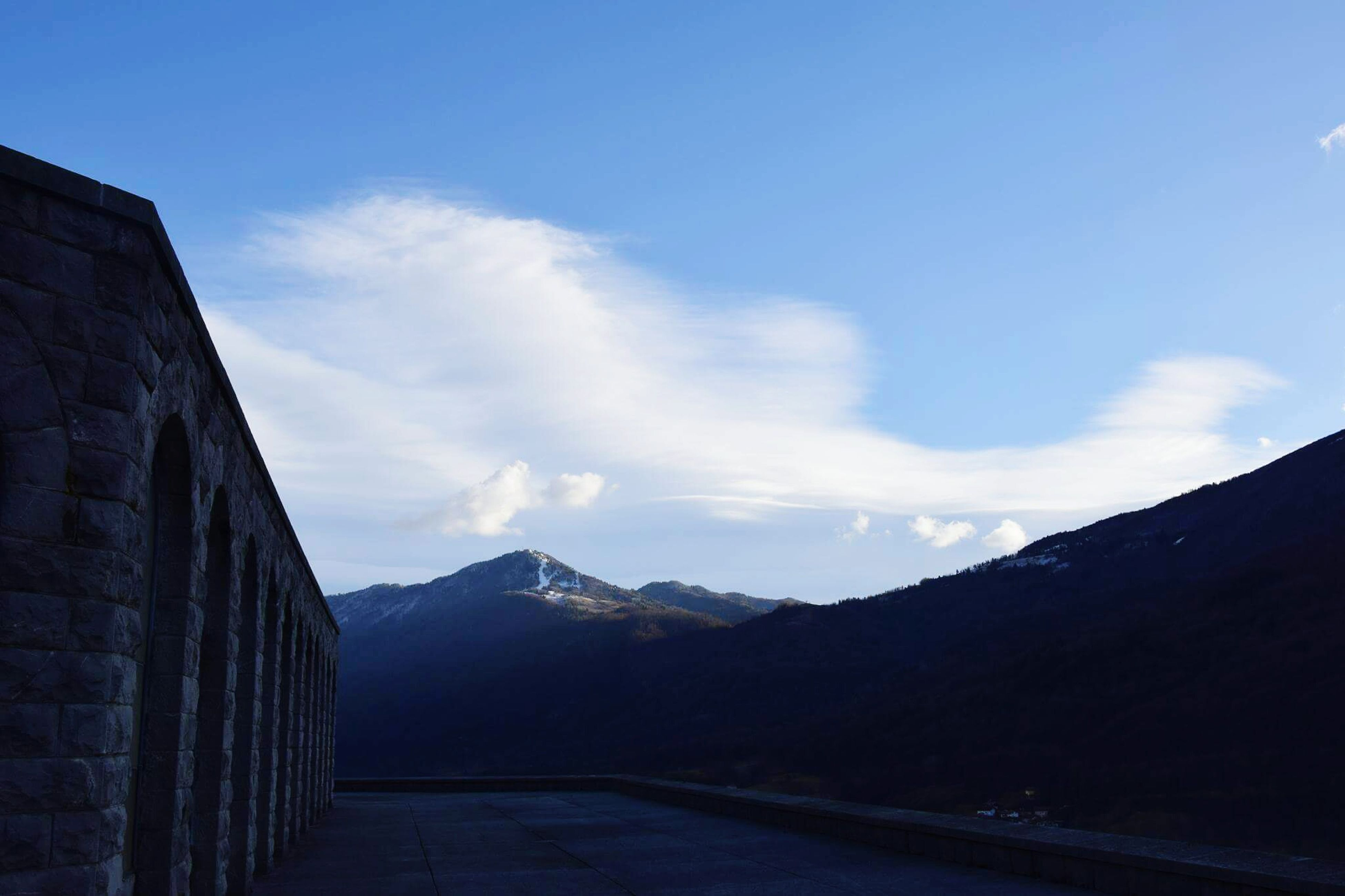 mountain, mountain range, sky, road, the way forward, tranquil scene, tranquility, cloud, cloud - sky, scenics, transportation, landscape, beauty in nature, nature, blue, outdoors, day, no people, non-urban scene, empty