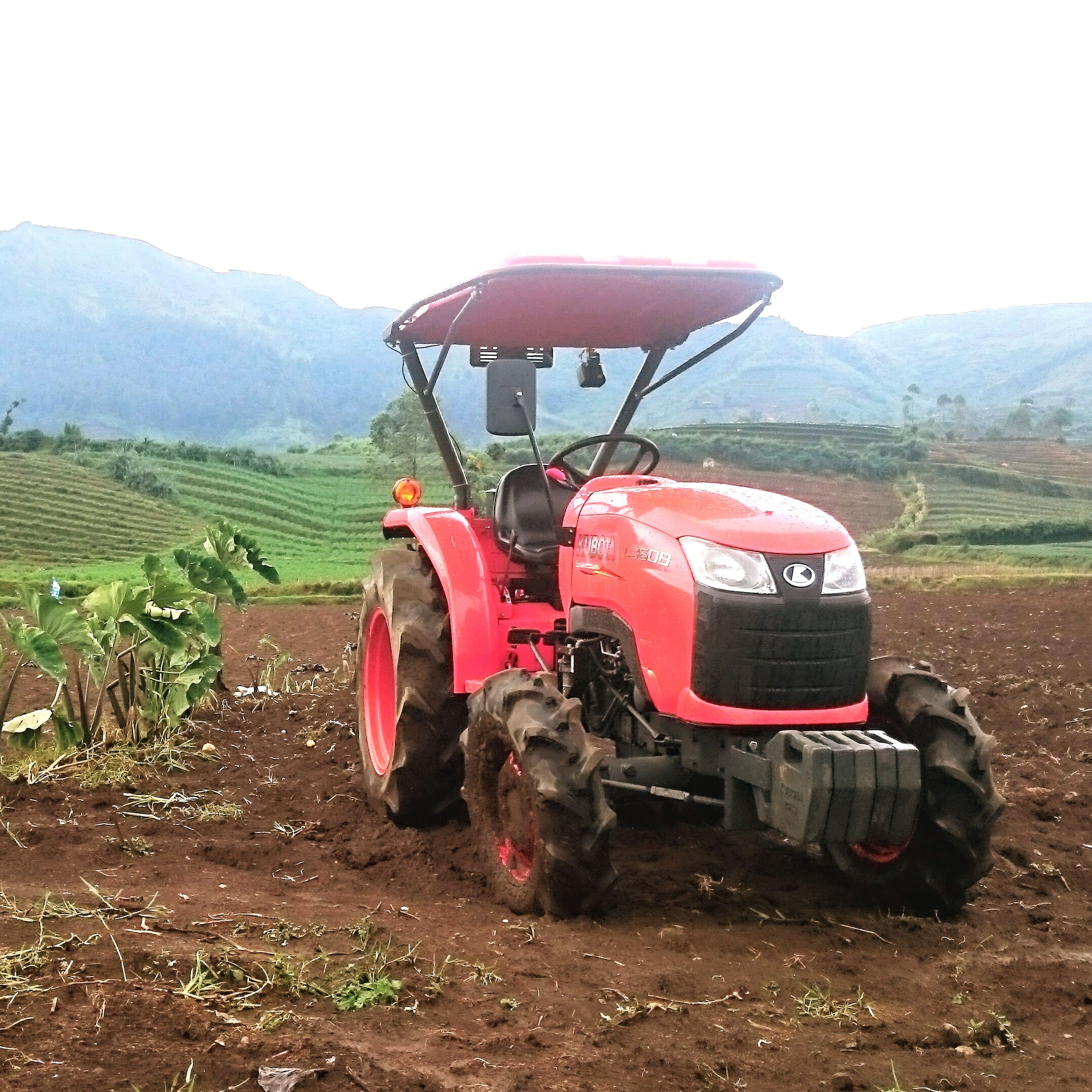 field, landscape, rural scene, land vehicle, agriculture, red, transportation, mode of transport, farm, mountain, grass, clear sky, car, tractor, nature, sky, day, outdoors, agricultural machinery, travel