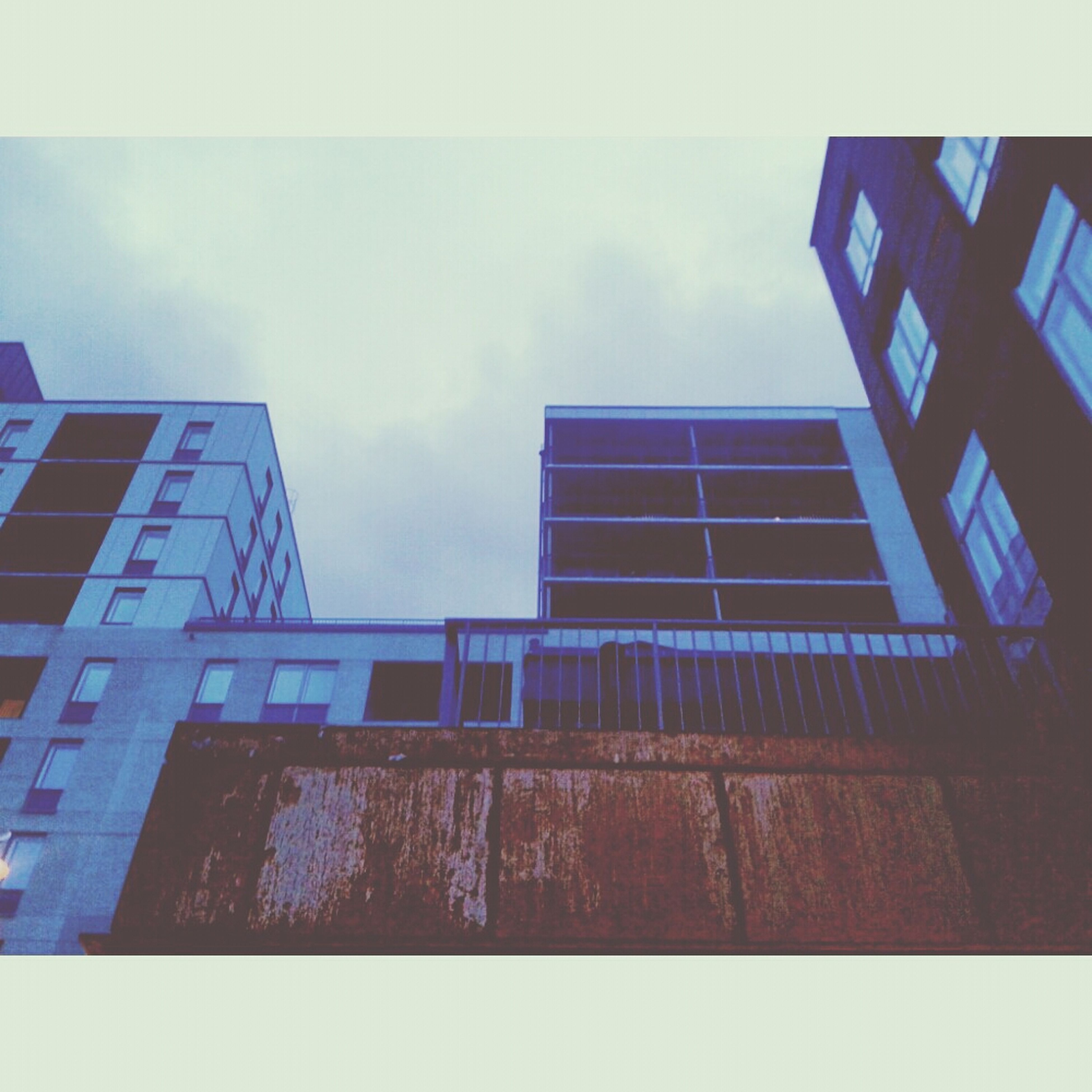 architecture, building exterior, built structure, low angle view, transfer print, sky, auto post production filter, building, window, cloud - sky, city, cloud, residential building, day, residential structure, outdoors, no people, glass - material, cloudy, blue