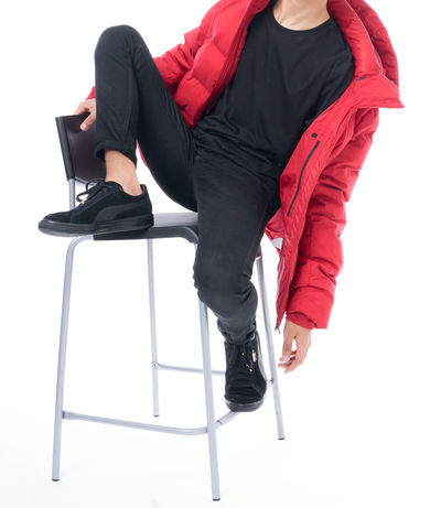 A teenager wearing red jacket , black top and bottom sitting isolated on white Studio Winter Clothes  Chair Cut Out Fashion Full Length Legs Crossed At Knee One Person Red Jacket Shoe Sitting Studio Shot Teenager Well-dressed White Background Young Adult