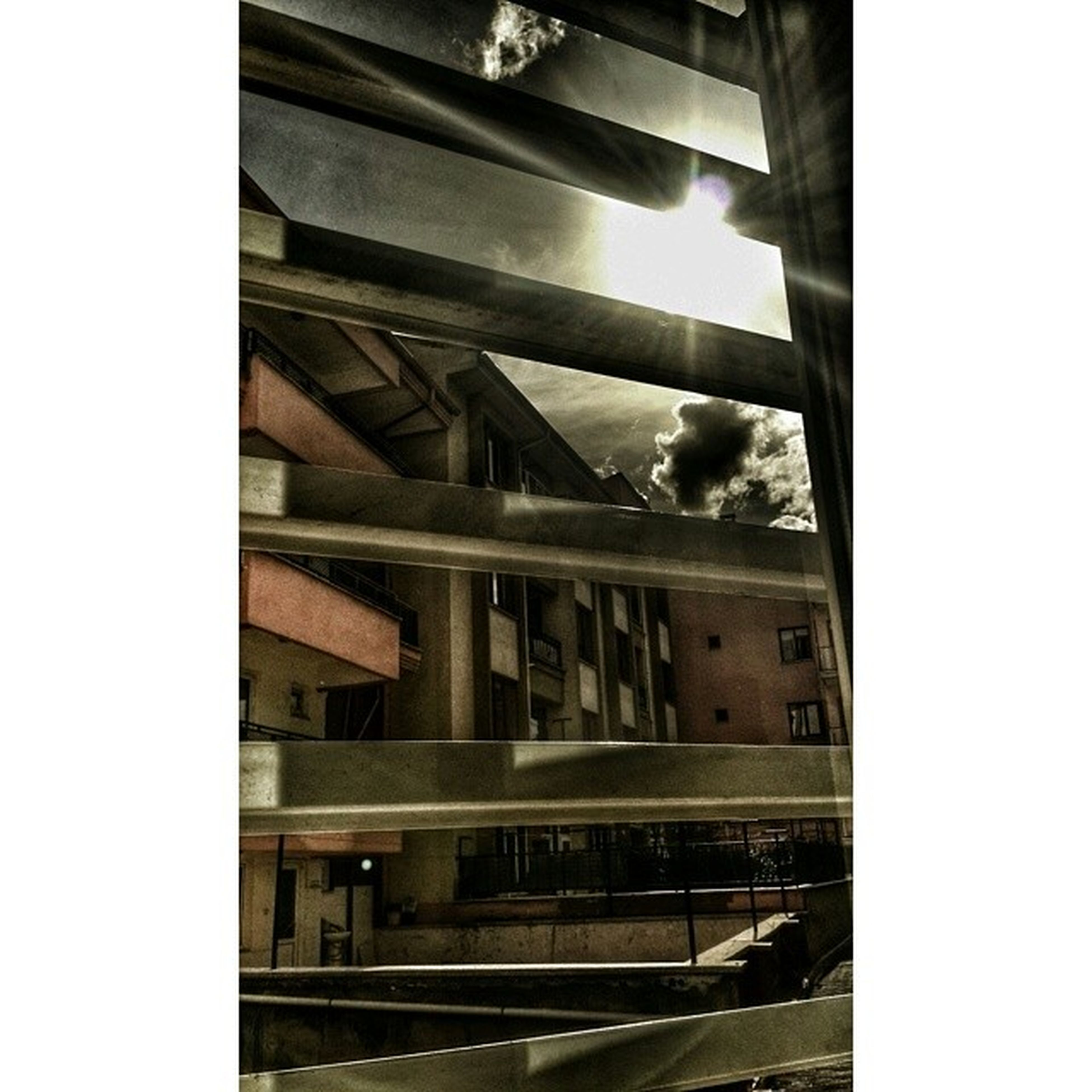 architecture, built structure, indoors, transfer print, low angle view, glass - material, window, building exterior, auto post production filter, reflection, transparent, bridge - man made structure, sky, railing, building, city, connection, day, no people, modern