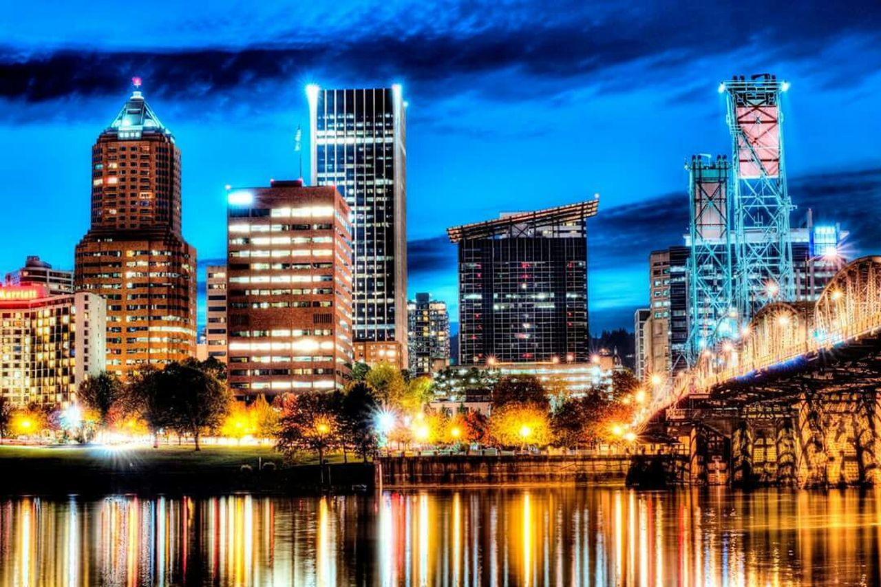 skyscraper, illuminated, architecture, modern, city, building exterior, cityscape, night, urban skyline, reflection, tower, built structure, city life, travel destinations, waterfront, sky, outdoors, no people, water, futuristic