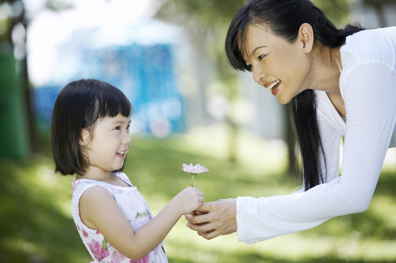 father playing with little daughter at park Beauty In Nature Black Hair Bonding Cheerful Child Childhood Cute Daughter Day Family Family With One Child Females Girls Give Flower Happiness Lifestyles Love Mother Mother's Day Outdoors Real People Smiling Togetherness Tree Women