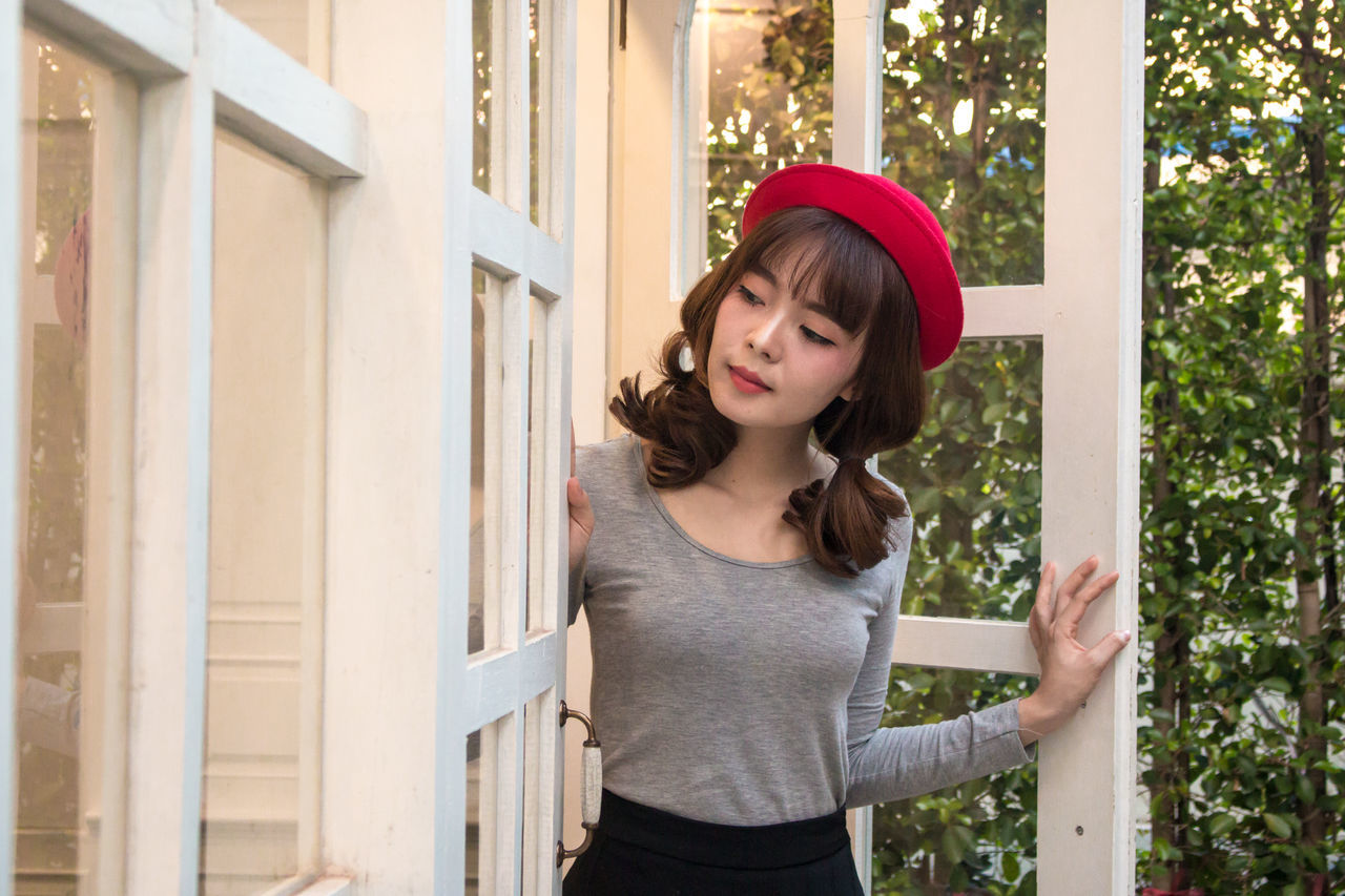 Young Woman Wearing Red Hat By Door