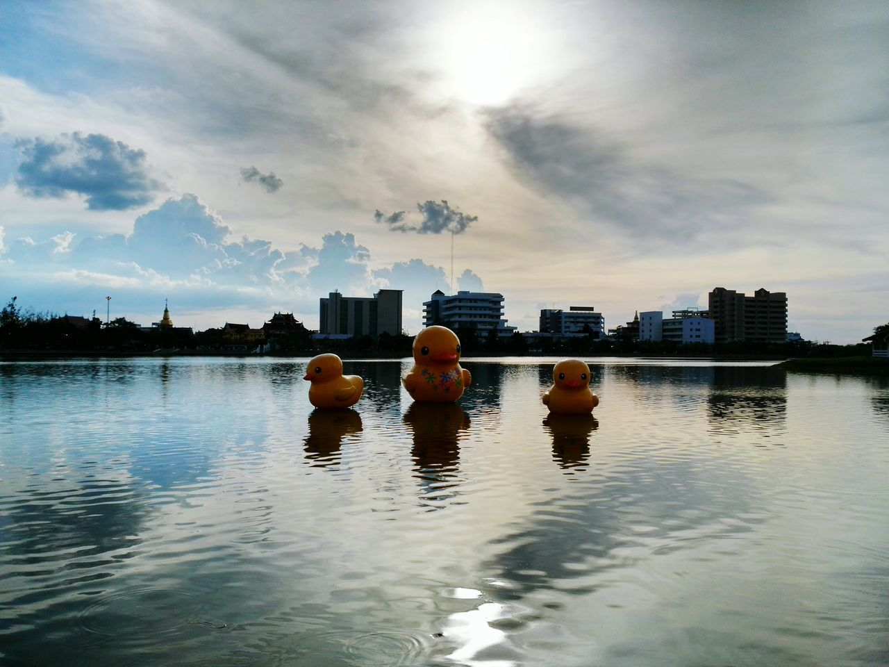 water, architecture, building exterior, built structure, cloud - sky, sky, reflection, skyscraper, waterfront, city, outdoors, men, day, modern, cityscape, people