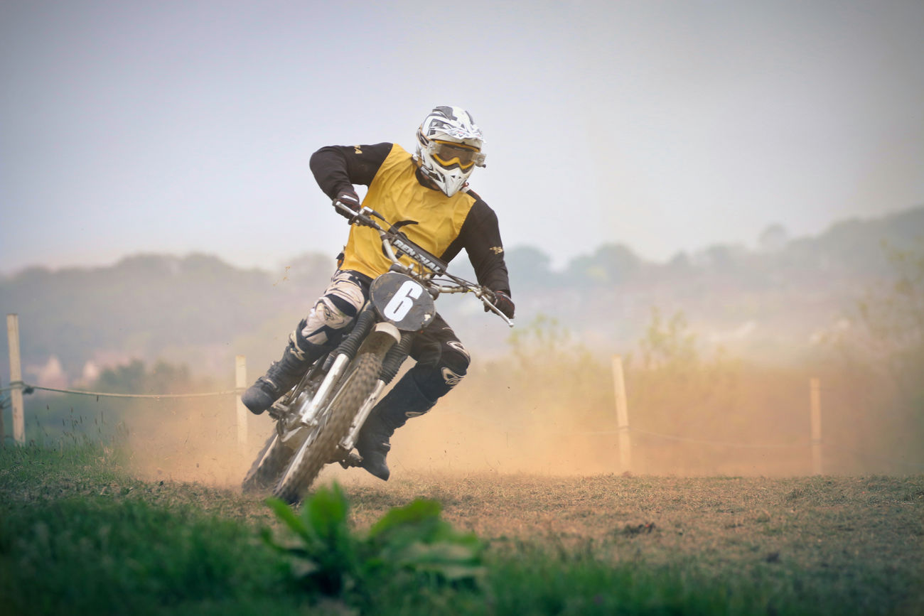 Motocross Rider Adult Adventure Competition Competitive Sport Day Field Grass Headwear Helmet Motion Motocross Motorcycle Motorcycle Racing Motorsport One Person Outdoors People Real People Riding Sky Speed Sport Sports Clothing Sports Helmet Sports Race