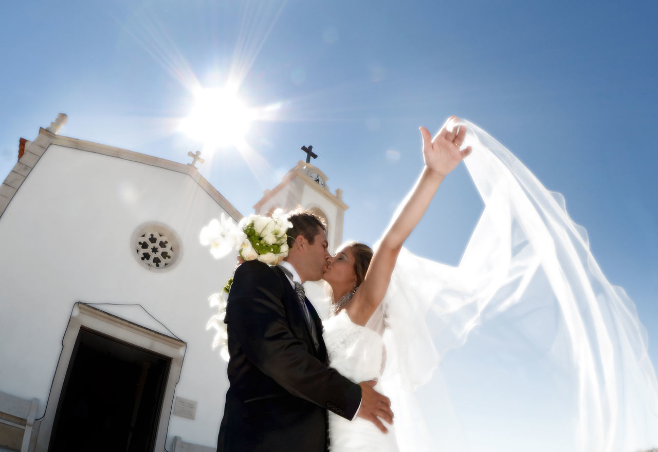 Wedding couple kissing in front of a church Architecture Bride Building Exterior Built Structure Couple - Relationship Day Lifestyles Love Low Angle View Outdoors Real People Religion Sky Spirituality Sunlight Togetherness Two People Wedding Wedding Dress BYOPaper! The Portraitist - 2017 EyeEm Awards EyeEmNewHere