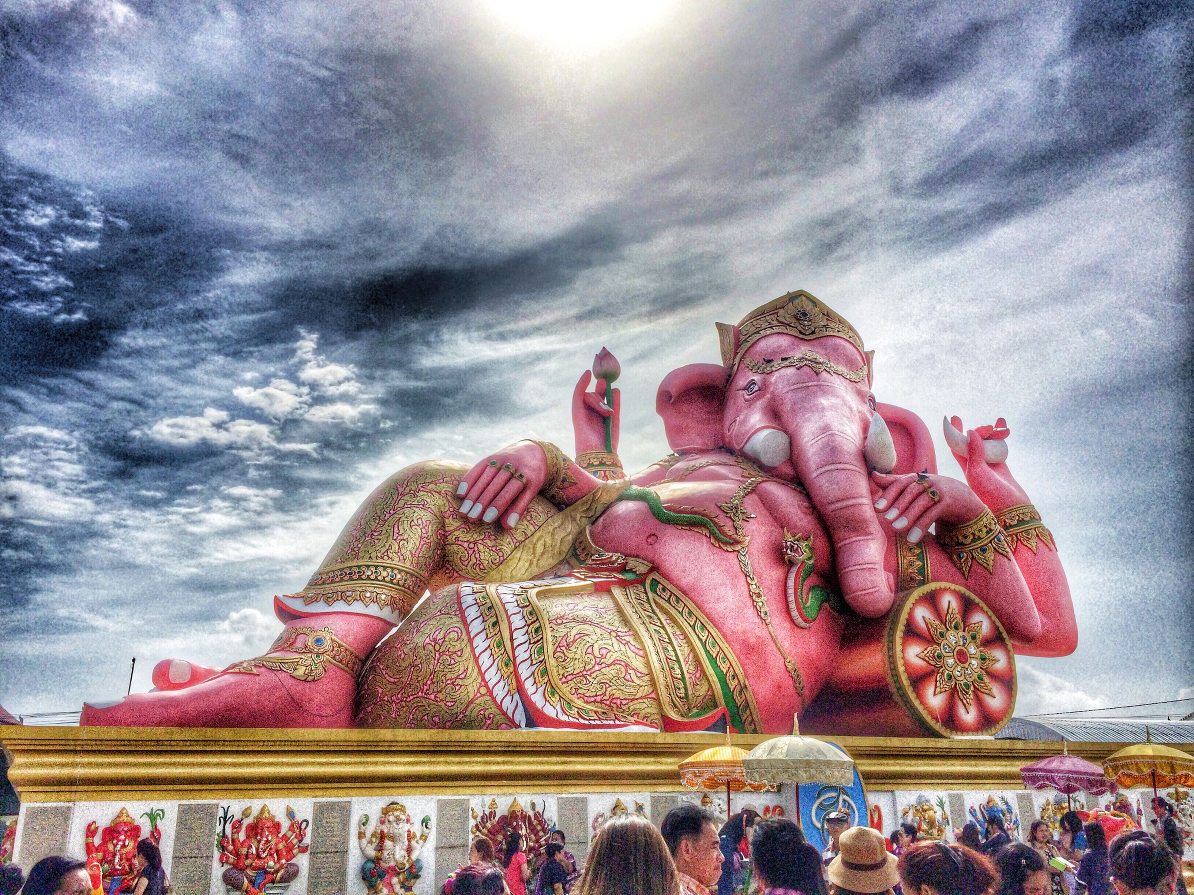 sky, low angle view, religion, cloud - sky, art and craft, art, spirituality, human representation, creativity, temple - building, cultures, place of worship, tradition, statue, cloudy, sculpture, built structure, cloud