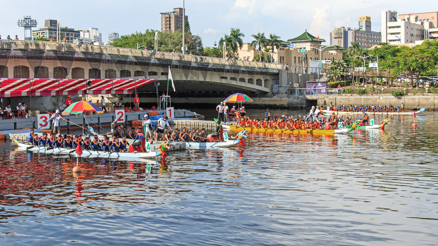 Kaohsiung, Taiwan, June 19, 2015: Boats racing in the Love River for the Dragon Boat Festival in Kaohsiung, Taiwan. The Dragon boats are the basis of the team paddling sport of dragon boat racing, a watersport which has its roots in an ancient folk ritual of contending villagers, which has been held for over 2000 years throughout southern China. For competition events, dragon boats are generally rigged with decorative Chinese dragon heads and tails. At other times (such as during training), decorative regalia is usually removed, although the drum often remains aboard for drummers to practice. Dragon boat races are traditionally held as part of the annual Duanwu Festival or Duen Ng observance in China and Taiwan. Architecture ASIA Building Exterior Built Structure Canal China City City Life Competition Day Dragon Boat Festival Hot Kaohsiung, Taiwan Leisure Activity Lifestyles Love River Market Stall Mixed Age Range Outdoors Rippled Sky Summer Taiwan Tropics Water