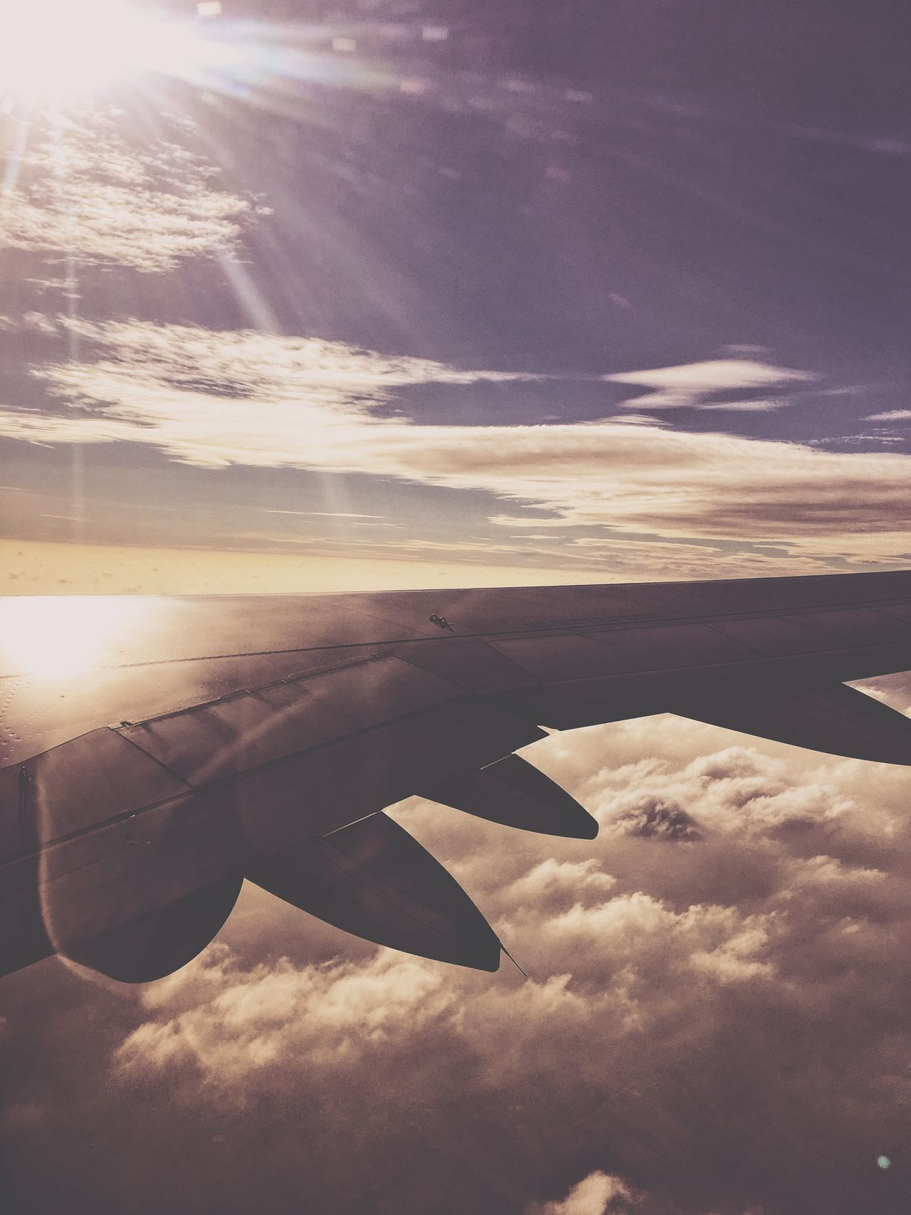 Airplane Flying Sky Cloud - Sky Sunset Transportation Aerial View Mid-air Beauty In Nature Aircraft Wing Sunlight No People Scenics Mode Of Transport Nature Sunbeam Cloudscape Air Vehicle Airplane Wing Outdoors IPhoneography IPhone