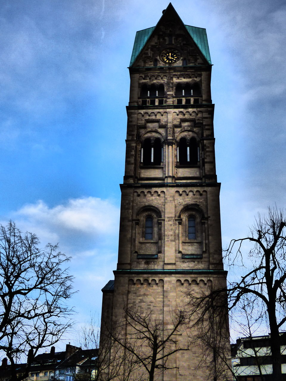 sky, cloud - sky, bare tree, low angle view, clock tower, tree, tower, religion, architecture, built structure, building exterior, day, place of worship, history, branch, no people, outdoors, spirituality, bell tower, nature, clock