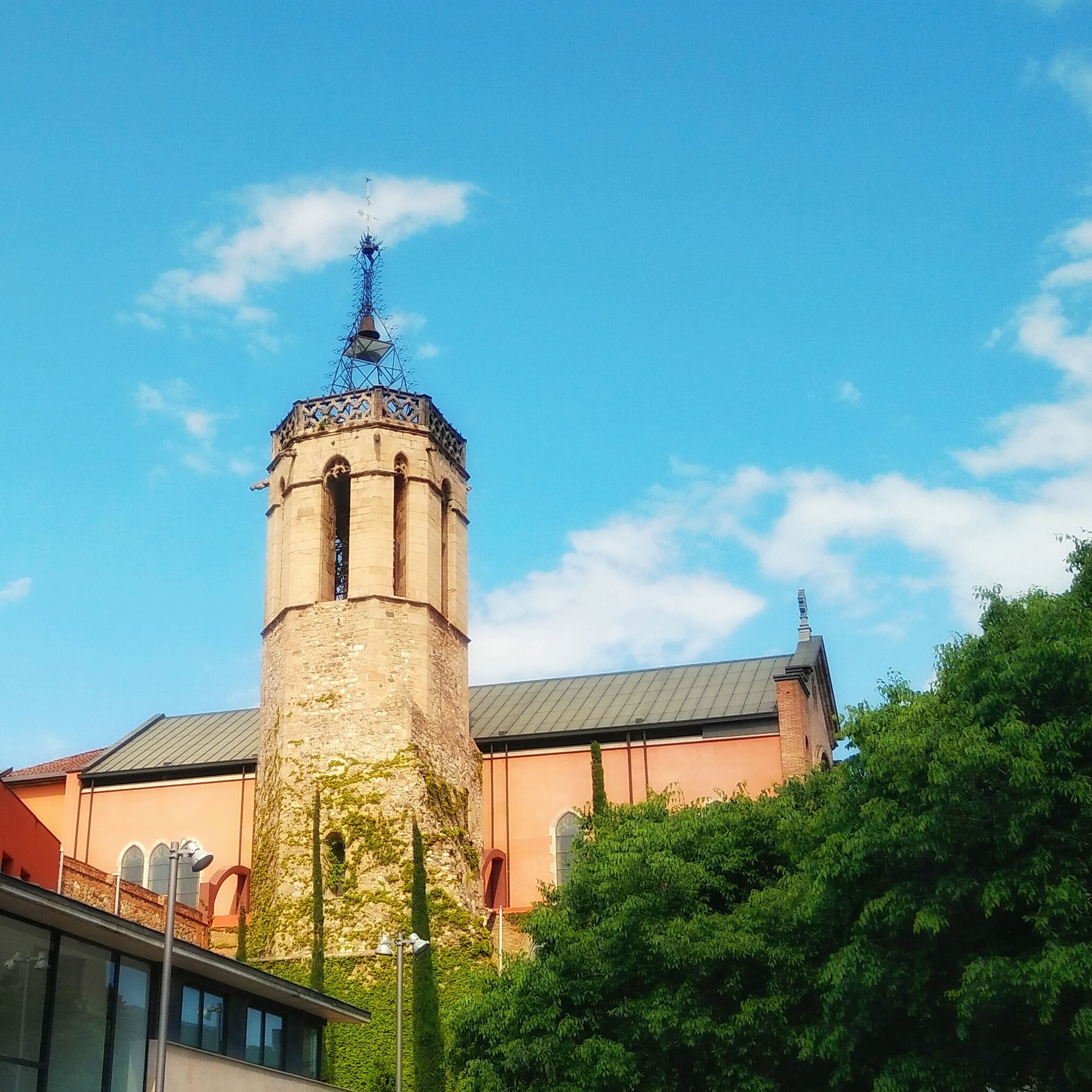 architecture, built structure, building exterior, sky, low angle view, tree, blue, cloud - sky, church, tower, religion, cloud, place of worship, history, day, outdoors, exterior, old, no people
