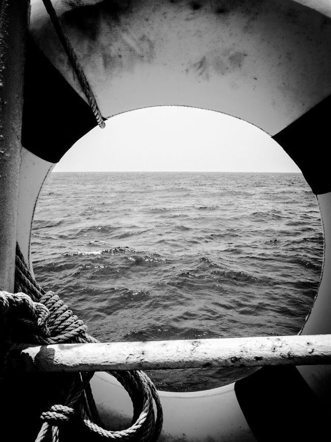 Seaview Black And White Sea Water Horizon Over Water Nautical Vessel Vacations No People On A Boat Boat Ride Boats Life Saving Equipment Life Saver Floatation Device Rope Boat Equipment Shiplife Boat Life Circular Window To The Sea Black & White Black And White Photography Ocean Ocean View Thailand