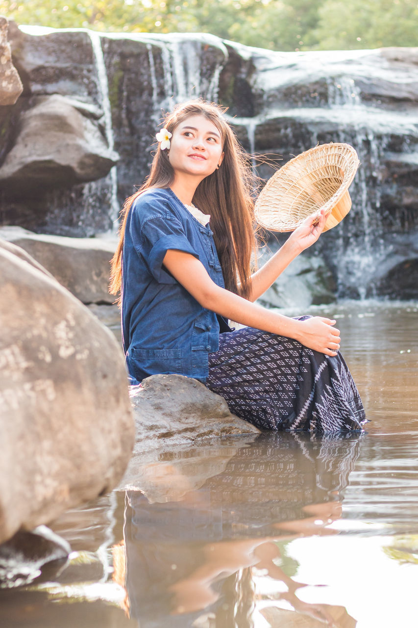 Young Woman Holding Hat While Sitting On Rock Against Waterfall