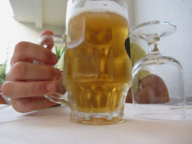 Male hand holding a cold mug of light beer Adult Alcohol Ale Beer Beverage Bubbles Cold Condensation Drink Drip Drop Foam Frosty Froth Glass Hand Jug Lager Light Liquid Man Mug Person Pint Refreshment