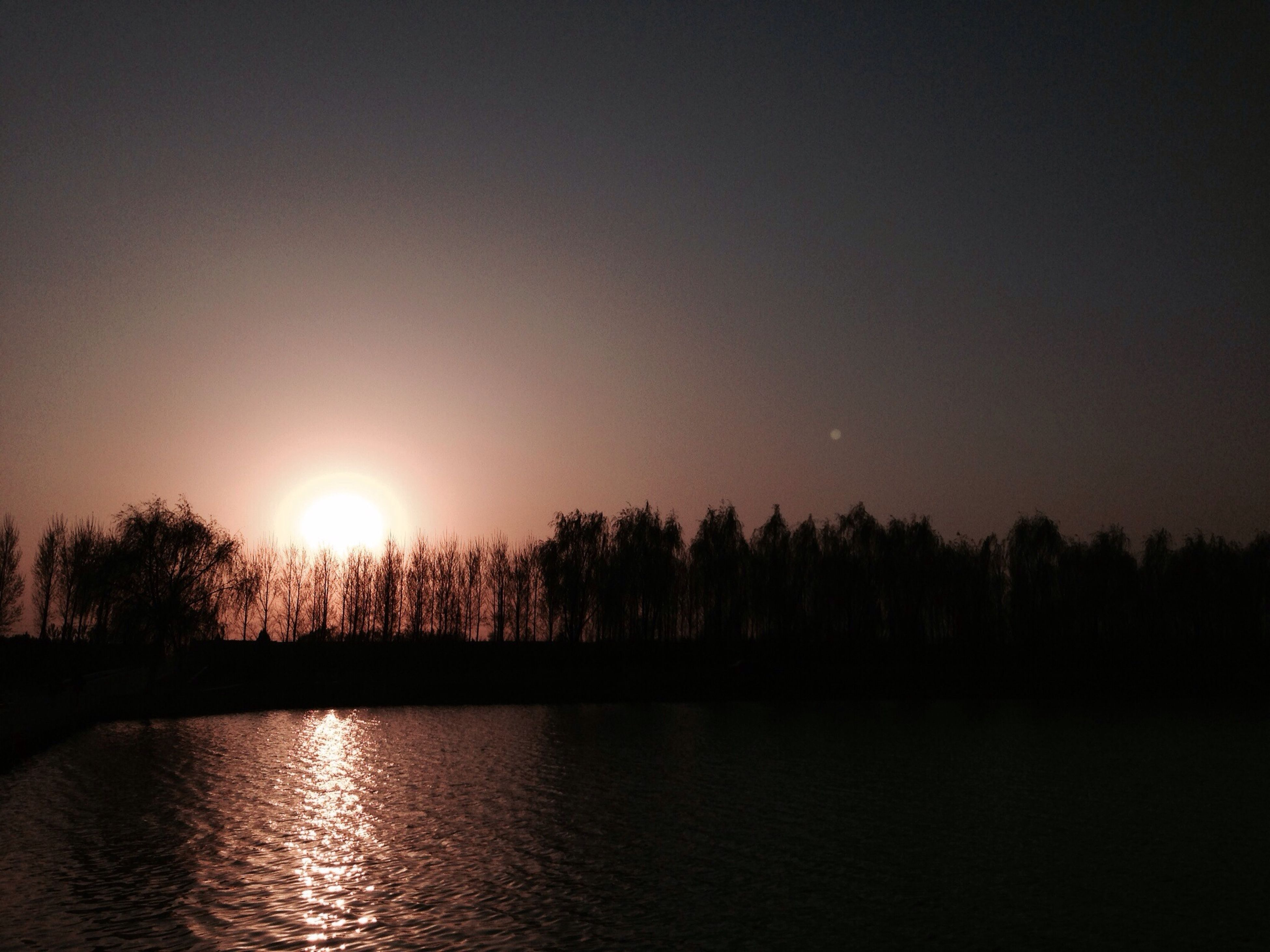 sunset, water, sun, tranquil scene, silhouette, tranquility, scenics, tree, beauty in nature, waterfront, reflection, lake, nature, idyllic, clear sky, sunlight, river, sky, copy space, outdoors