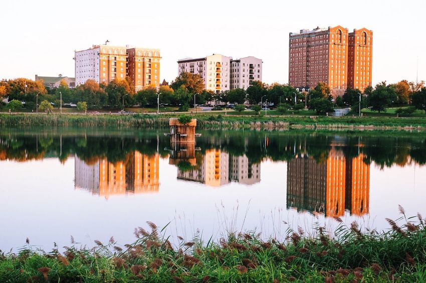 Architecture Building Exterior Built Structure City City Life Cityscape Crowded Distant Geometry Horizontal Symmetry Lake Outdoors Reflection Relaxing Moments Residential District Residential Structure River Standing Water Symmetry Tree Tropical Climate Water Waterfront