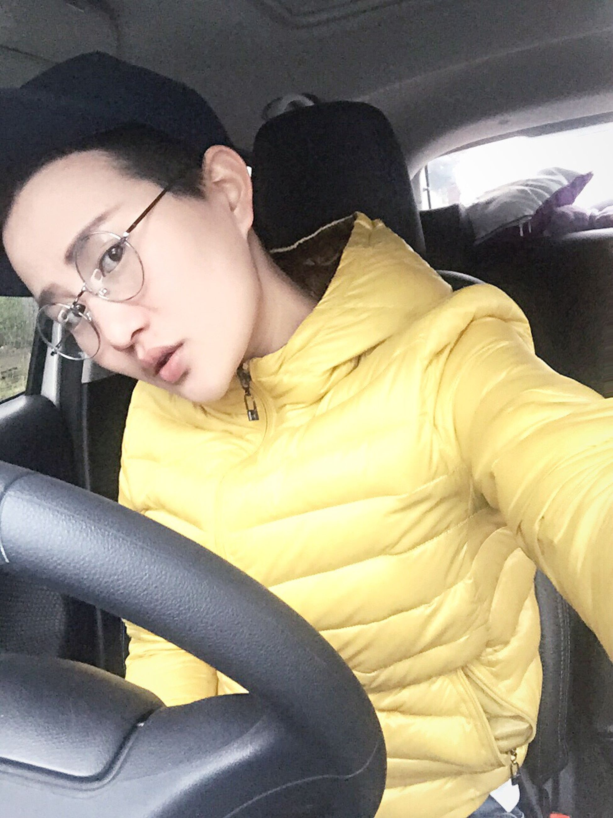 indoors, technology, person, sitting, lifestyles, young adult, vehicle interior, casual clothing, transportation, relaxation, front view, mode of transport, home interior, vehicle seat, leisure activity, wireless technology, young men, three quarter length