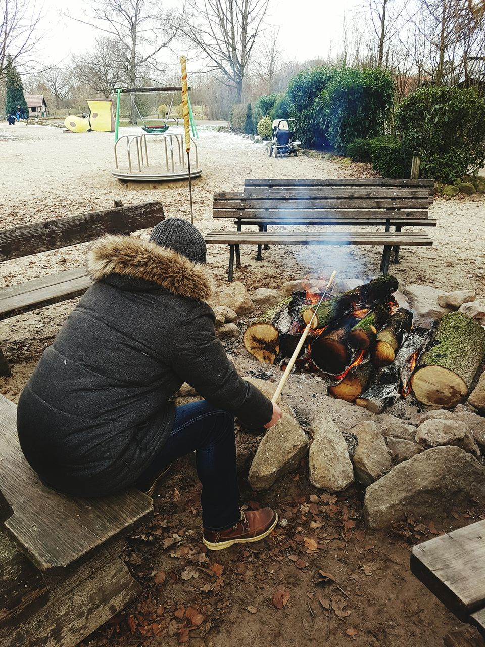 Man Cooking Meat At Bonfire On Playground During Winter