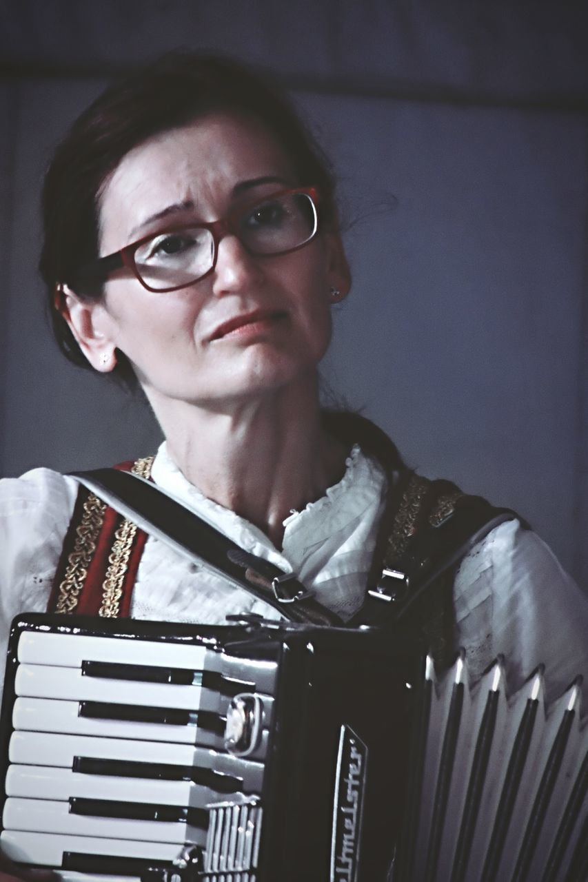 accordion, music, real people, mid adult, one person, eyeglasses, playing, looking at camera, musical instrument, musician, lifestyles, young adult