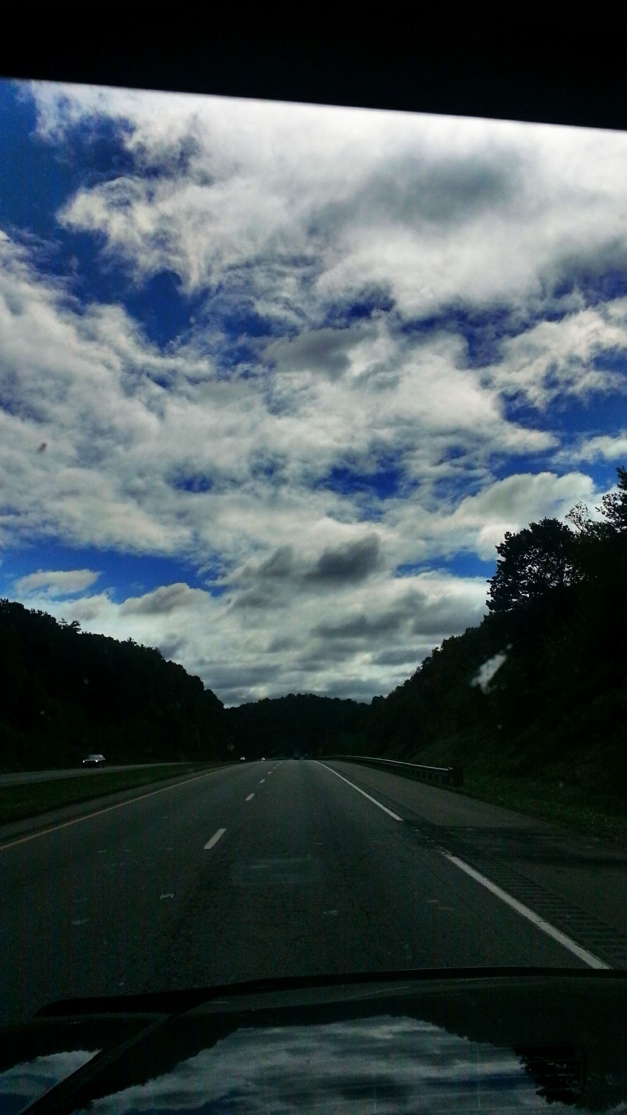 transportation, road, sky, the way forward, country road, road marking, landscape, cloud - sky, diminishing perspective, car, cloud, vanishing point, tree, tranquil scene, vehicle interior, windshield, nature, tranquility, mountain, land vehicle