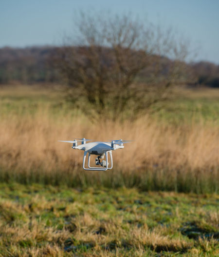 DJI Phantom 4 pro quadcopter drone flying with a camera against blue sky. Drone  Fly Landing Noise Quadcopter Remote Control Aerial Aircraft Aircraft Noise Approval Aviation Buoyancy Concept Departure Driver License Drones Regulation Exploration Flight Mandatory Marking Propeller Rotors Steer TakeOff Video Drone Visibility