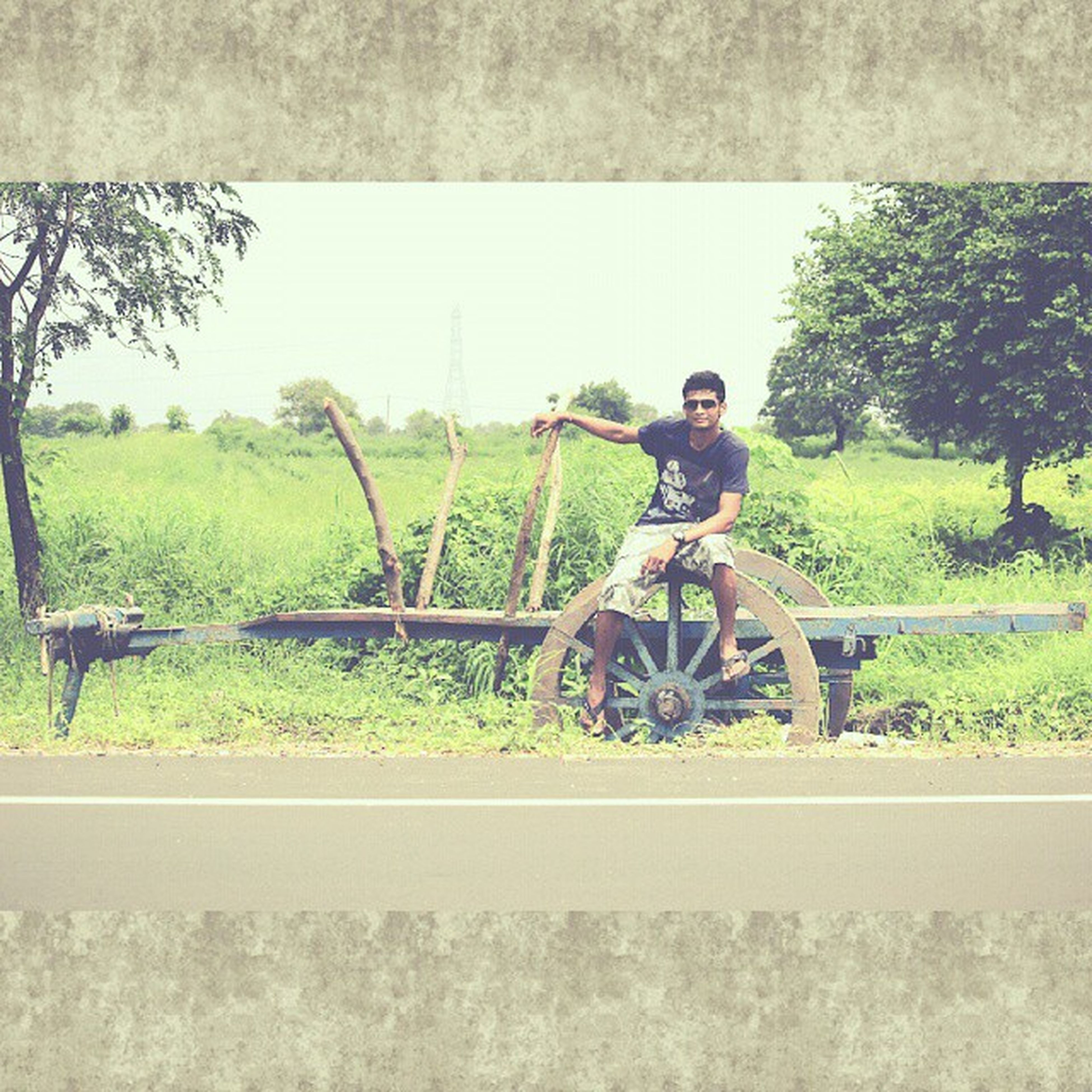 lifestyles, leisure activity, grass, tree, full length, field, casual clothing, person, bicycle, clear sky, green color, transportation, young adult, day, childhood, nature, standing, landscape