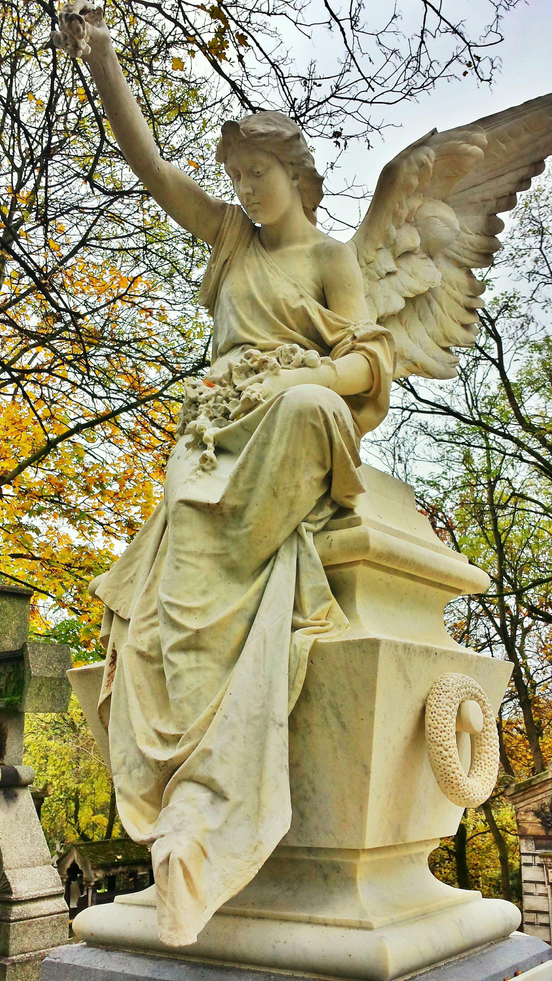 statue, human representation, sculpture, art and craft, art, creativity, tree, low angle view, famous place, religion, travel destinations, carving - craft product, angel, craft, travel, spirituality, tourism, sky