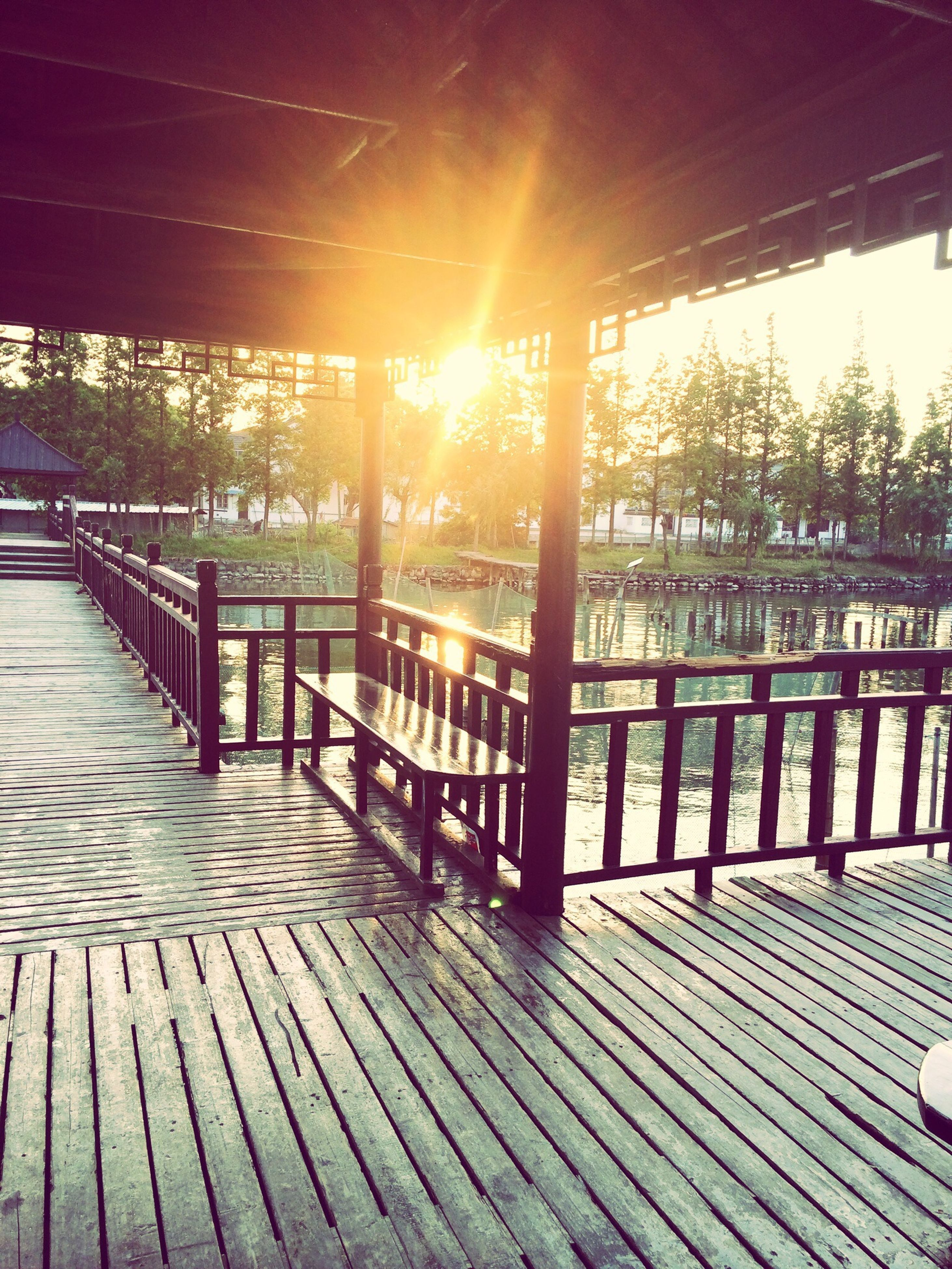 sunlight, railing, tree, shadow, sun, wood - material, tranquility, bench, empty, tranquil scene, sunbeam, nature, water, absence, pier, built structure, sunset, sky, no people, outdoors