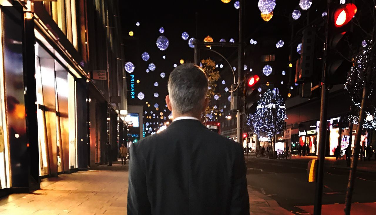 rear view, illuminated, night, one person, real people, men, building exterior, built structure, city, architecture, outdoors, one man only, adult, people